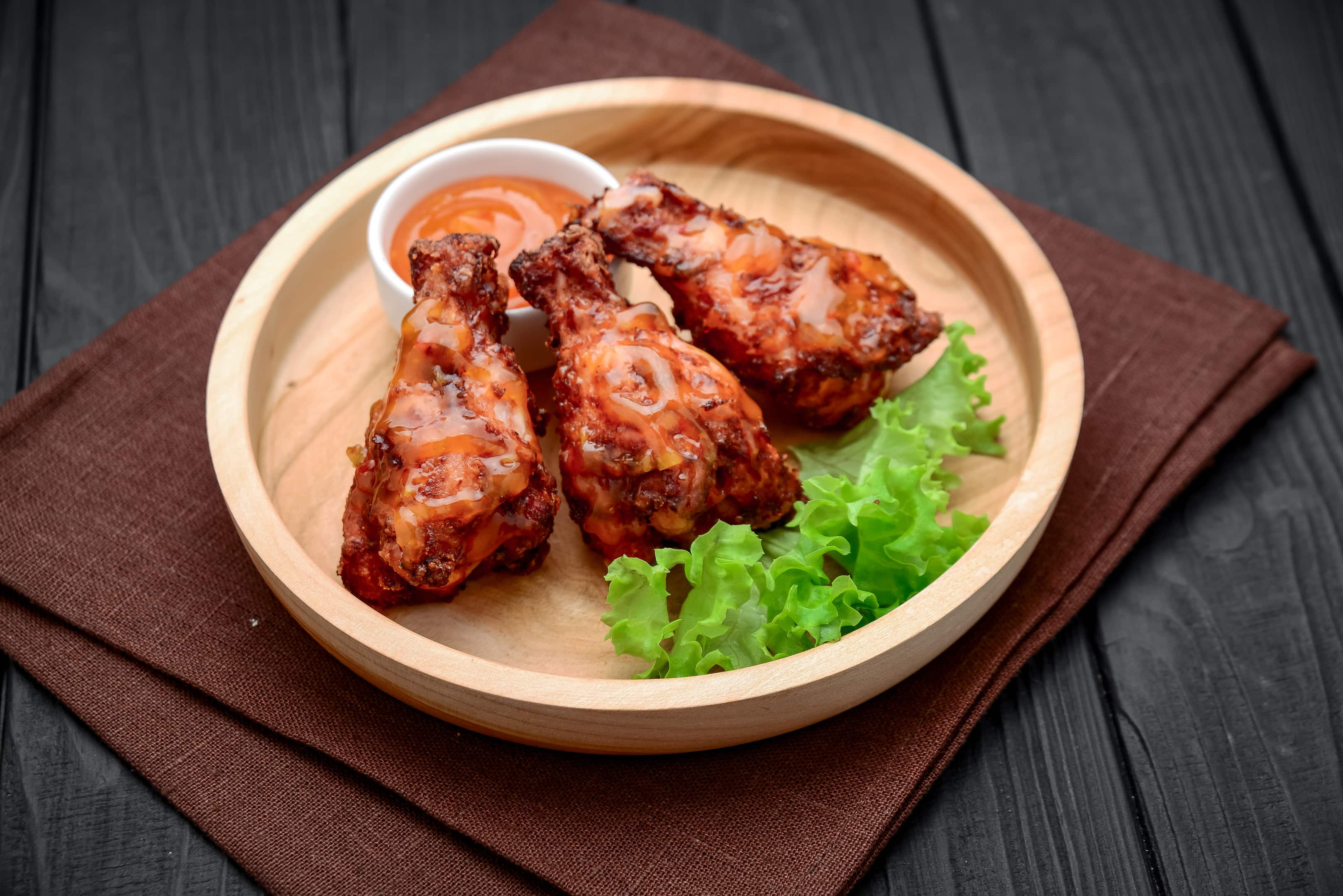 Caribbean jerk chicken wings with spicy chili sauce on wooden plate