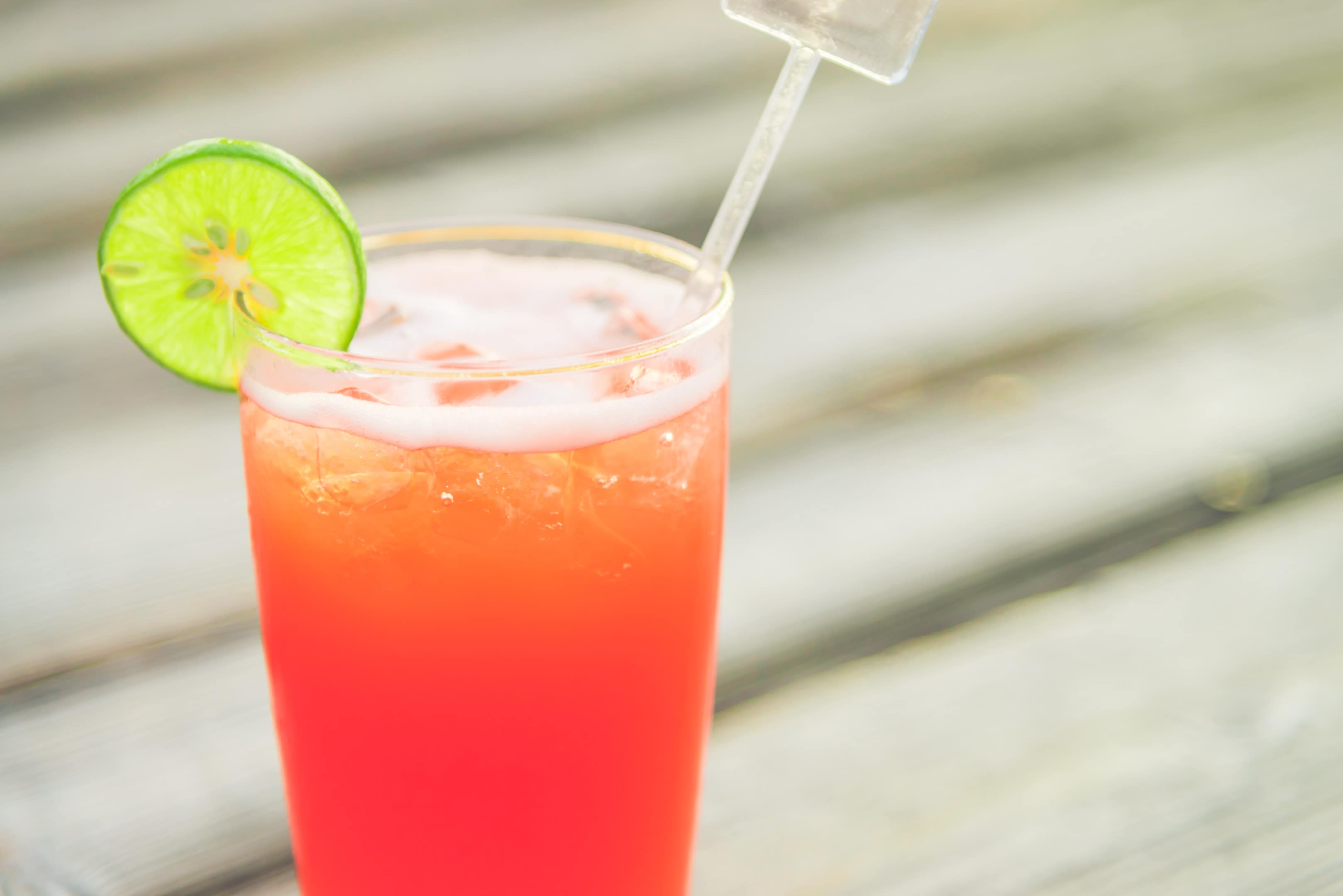 Caribbean rum punch with lime on wooden table