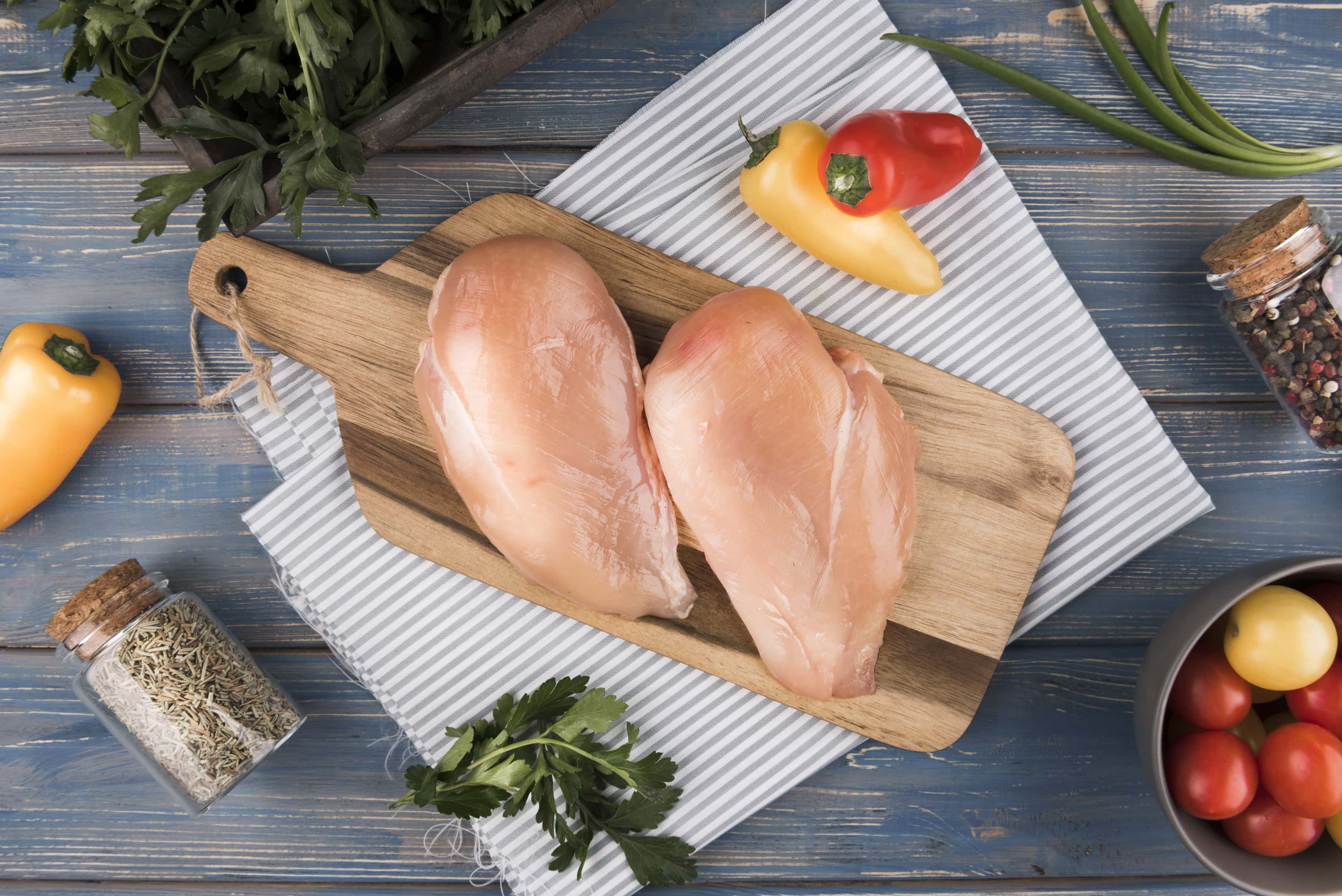 Chicken breasts on wooden board with ingredients