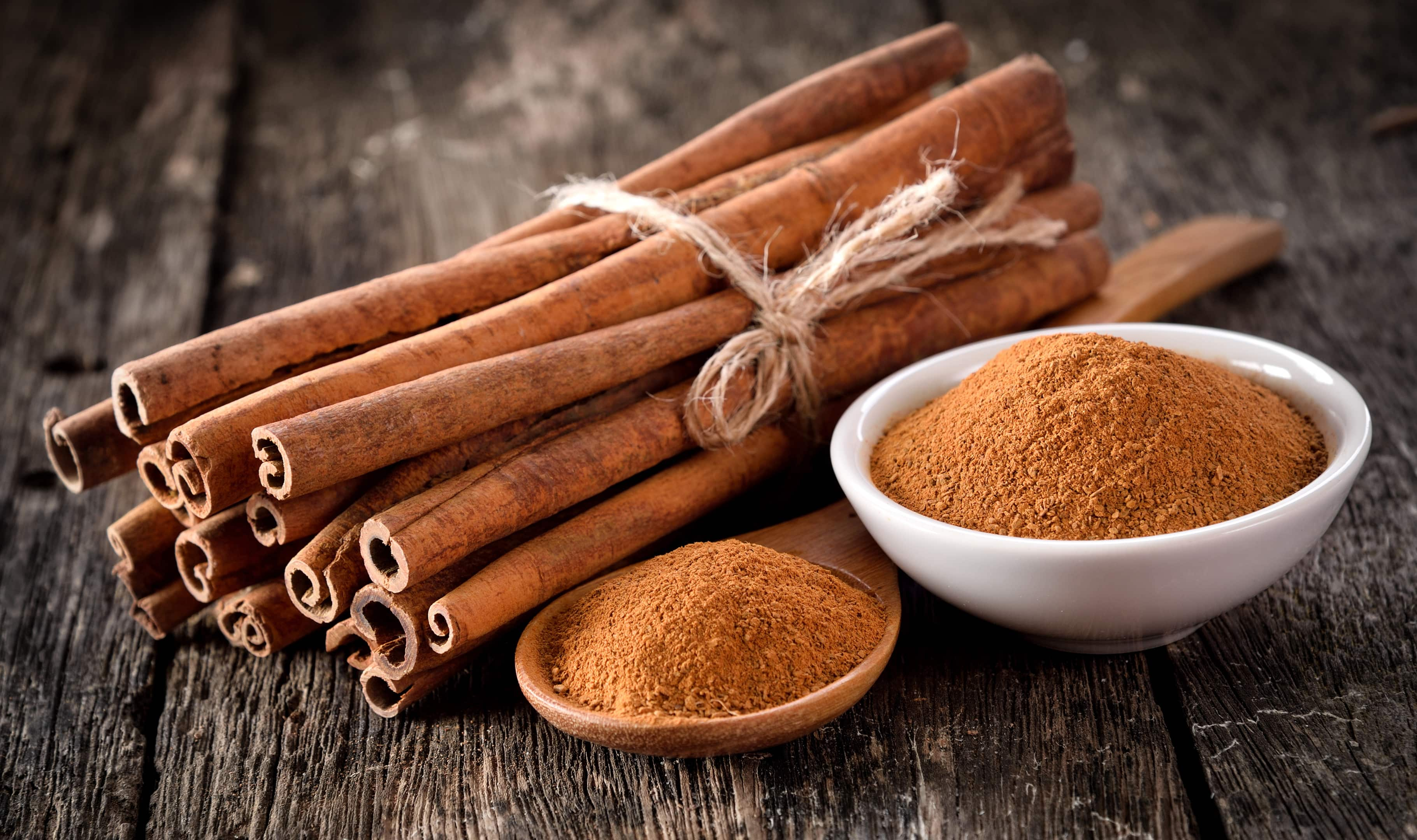 Cinnamon sticks and powder on table wooden