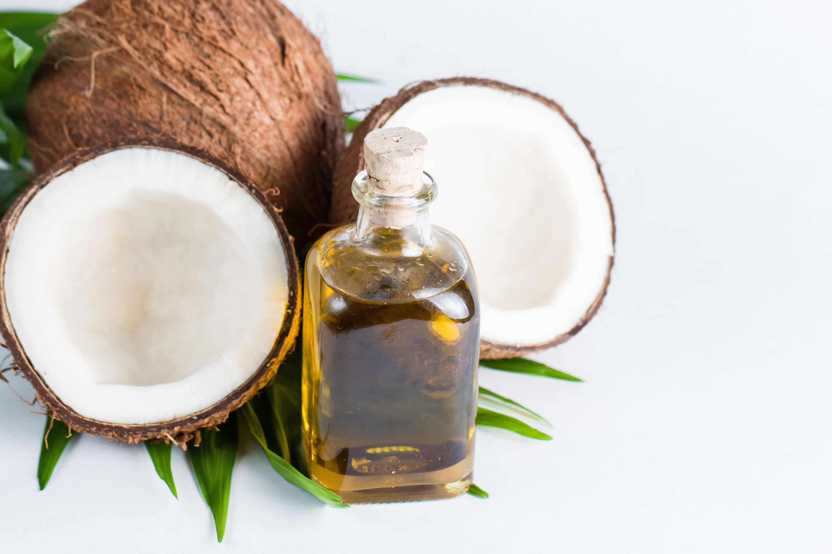 Coconut oil with fresh coconut on white background