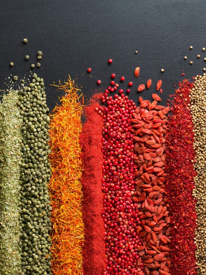 Colorful collection of spices and herbs on black table