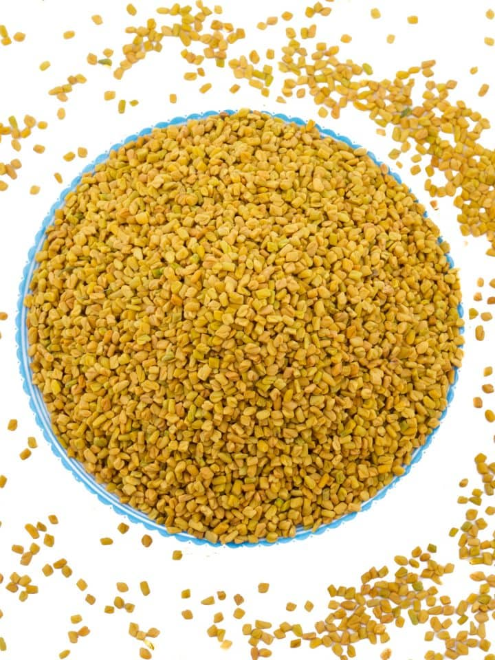 Fenugreek seeds in blue bowl on isolated white background