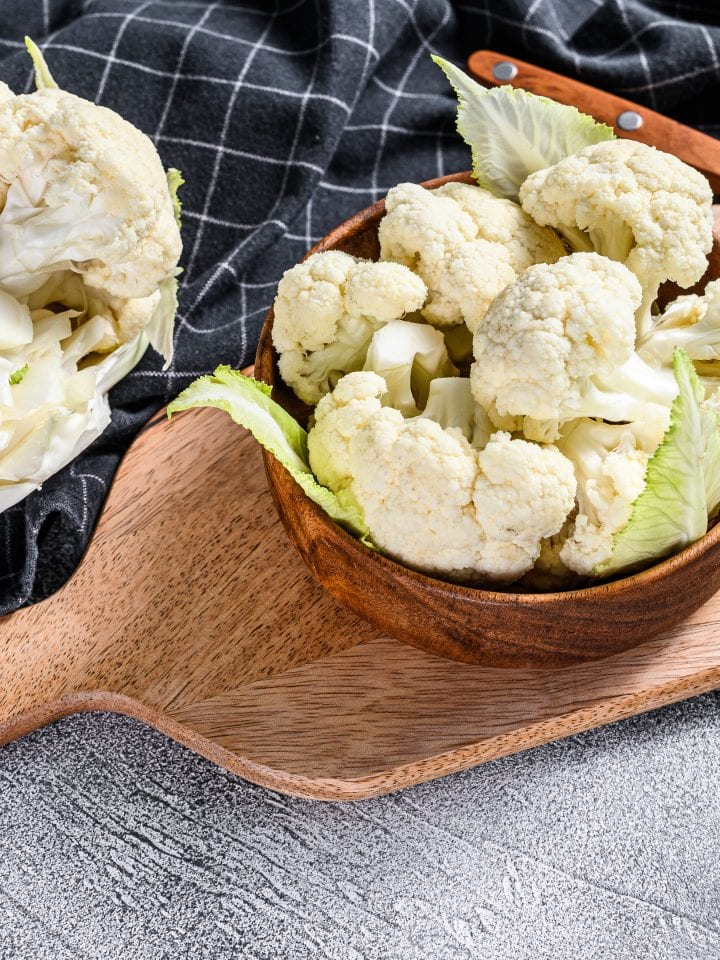 Fresh cauliflower cut into small pieces in wooden bowl