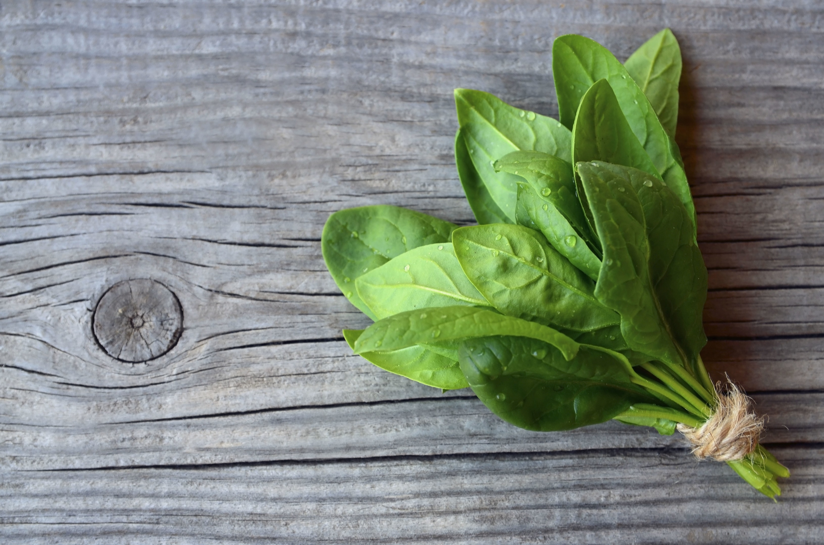 Fresh green organic spinach bundle leaves old wooden table