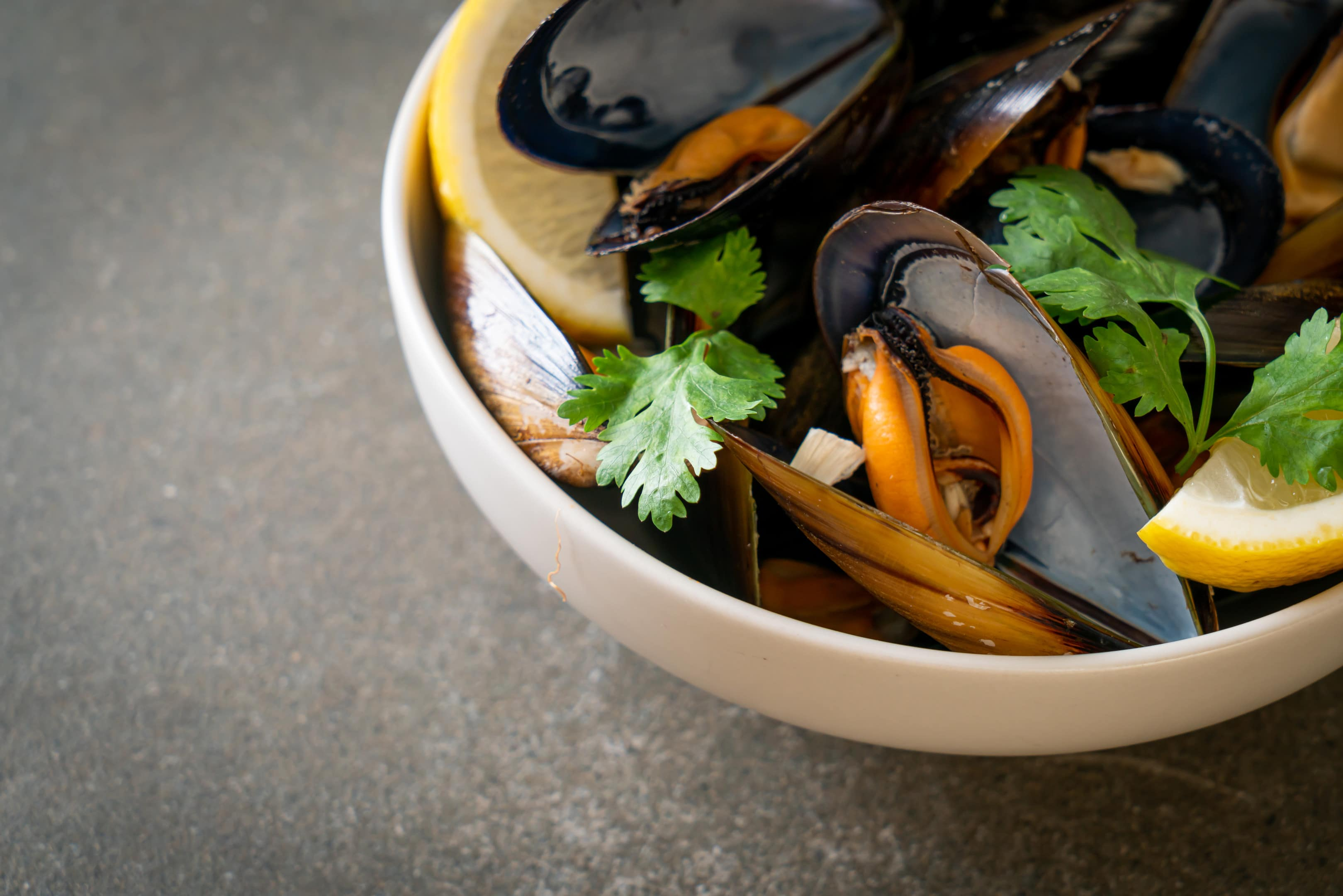 Fresh mussels with herbs in bowl