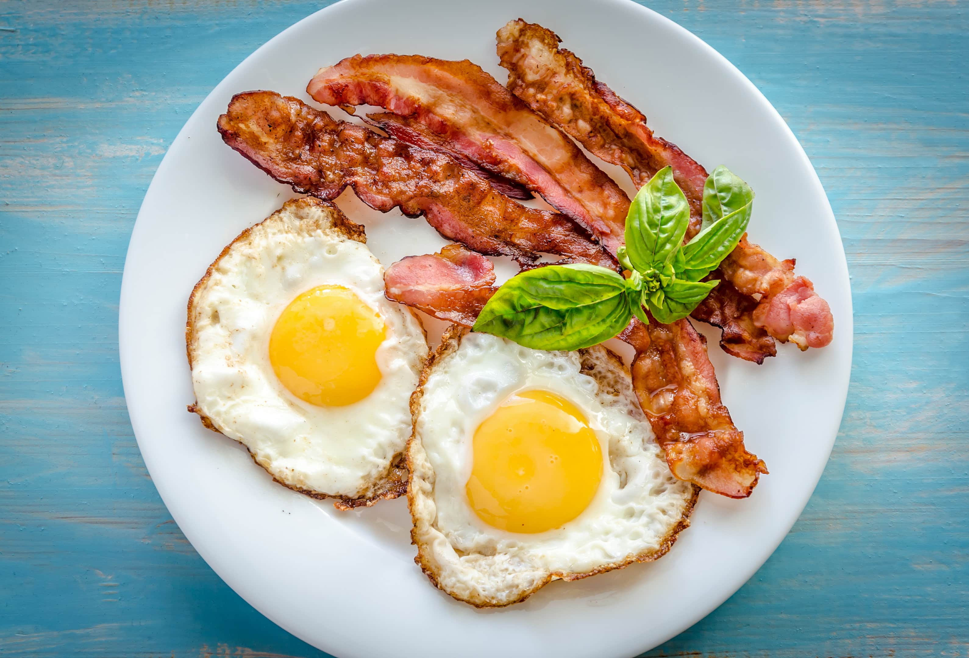 Fried eggs with fried bacon on wooden table