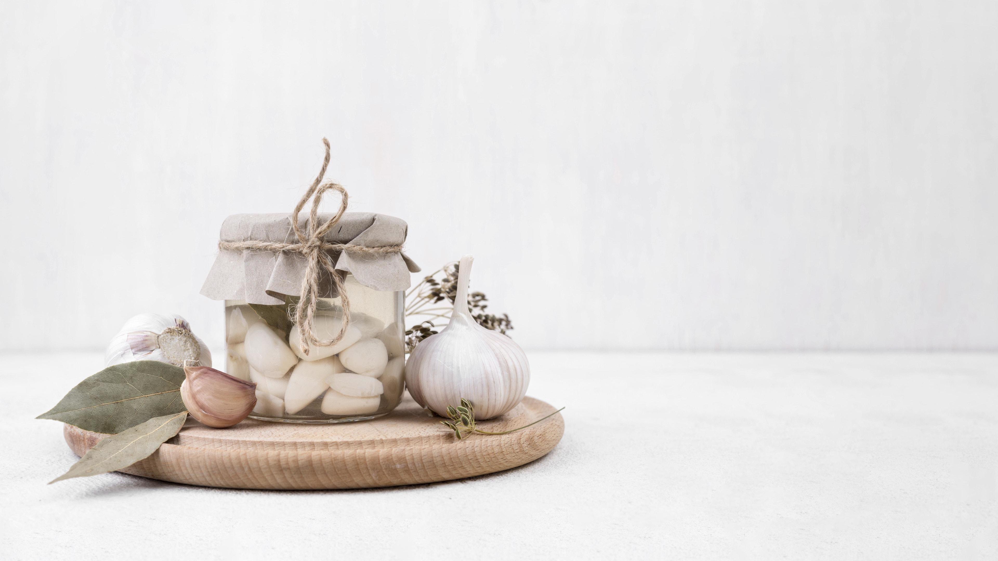 Garlic cloves with jar of peeled garlic