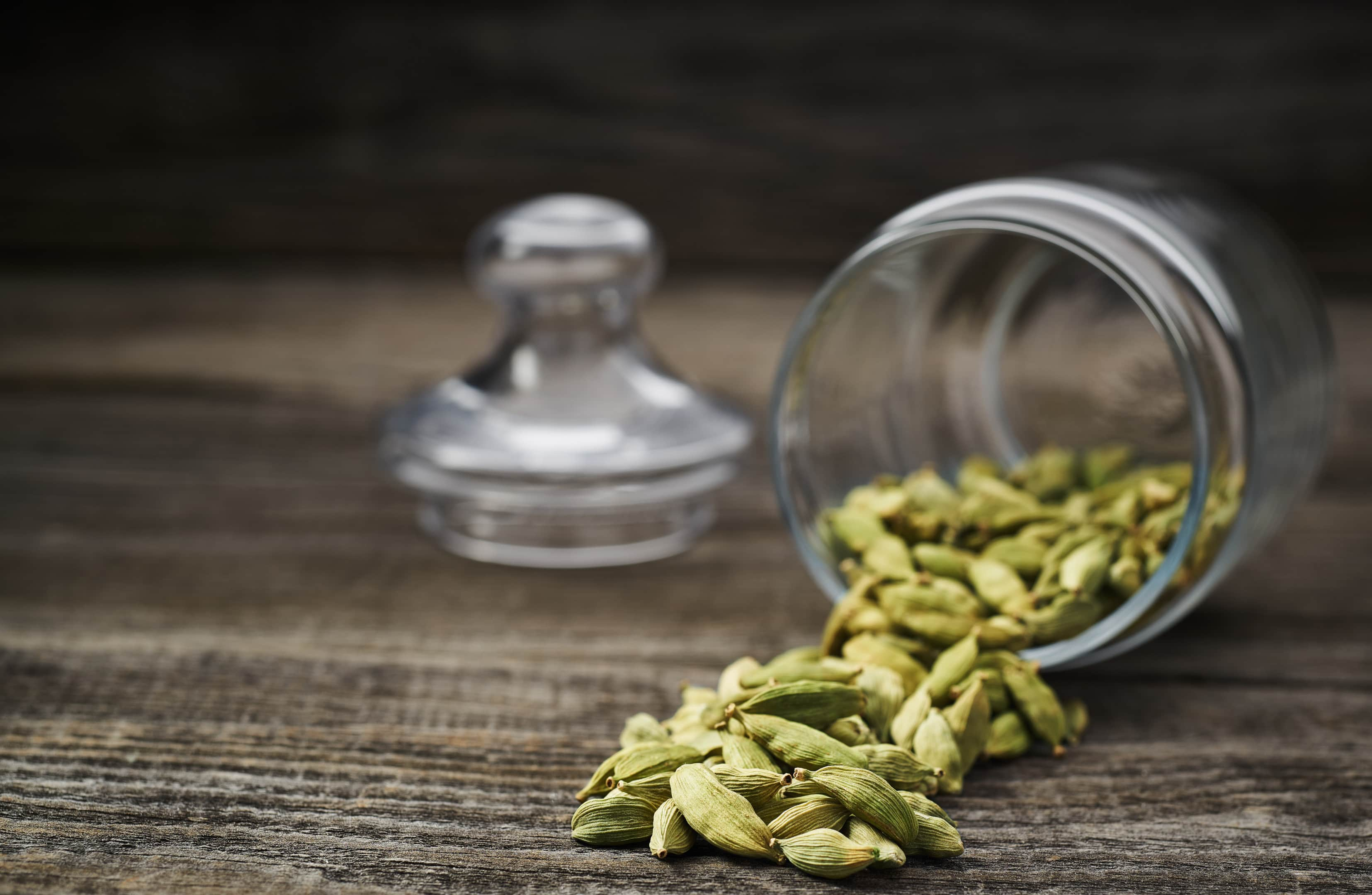Green cardamom pods spill from glass jar on wooden table