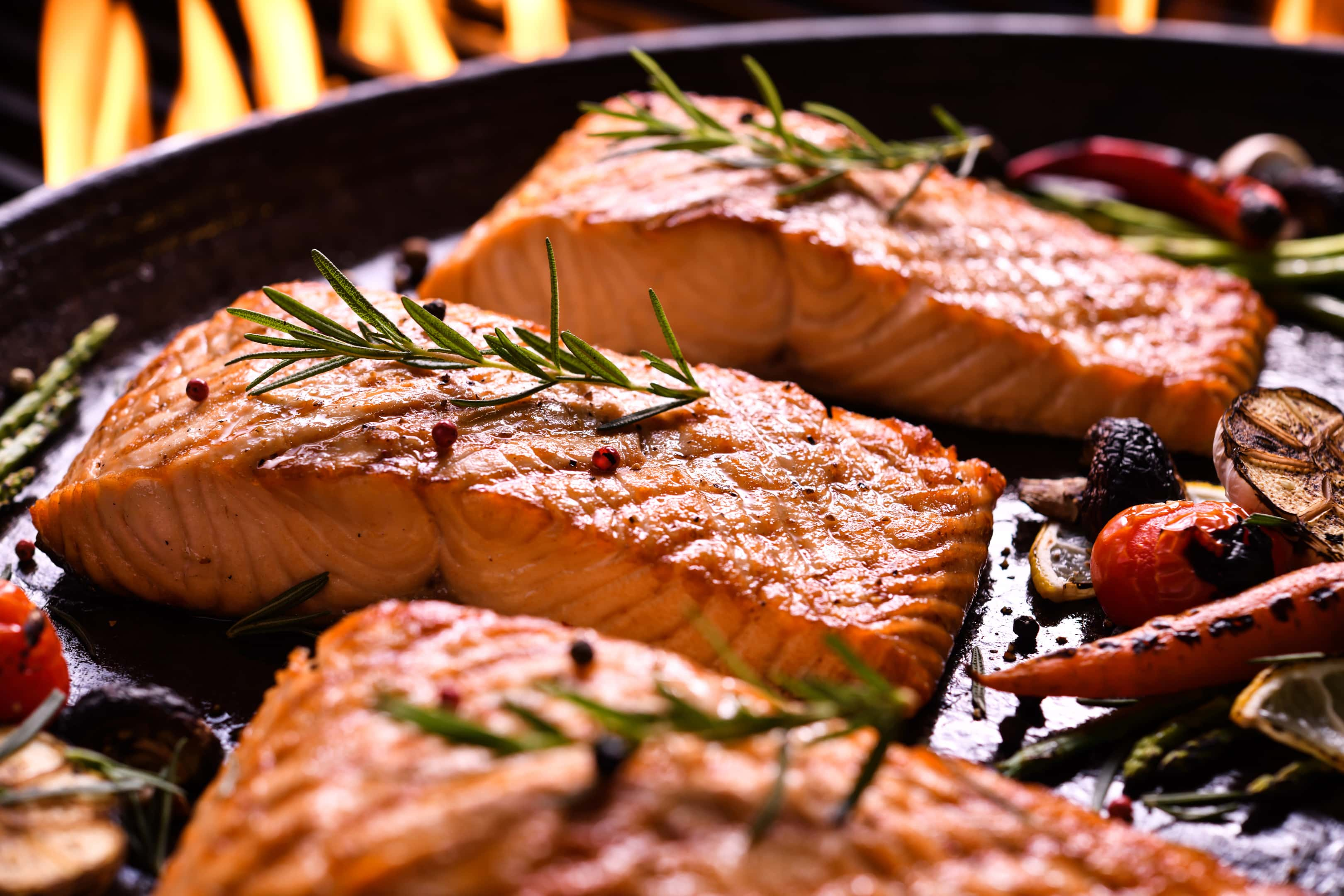 Grilled salmon fish with various vegetables in pan on flaming grill