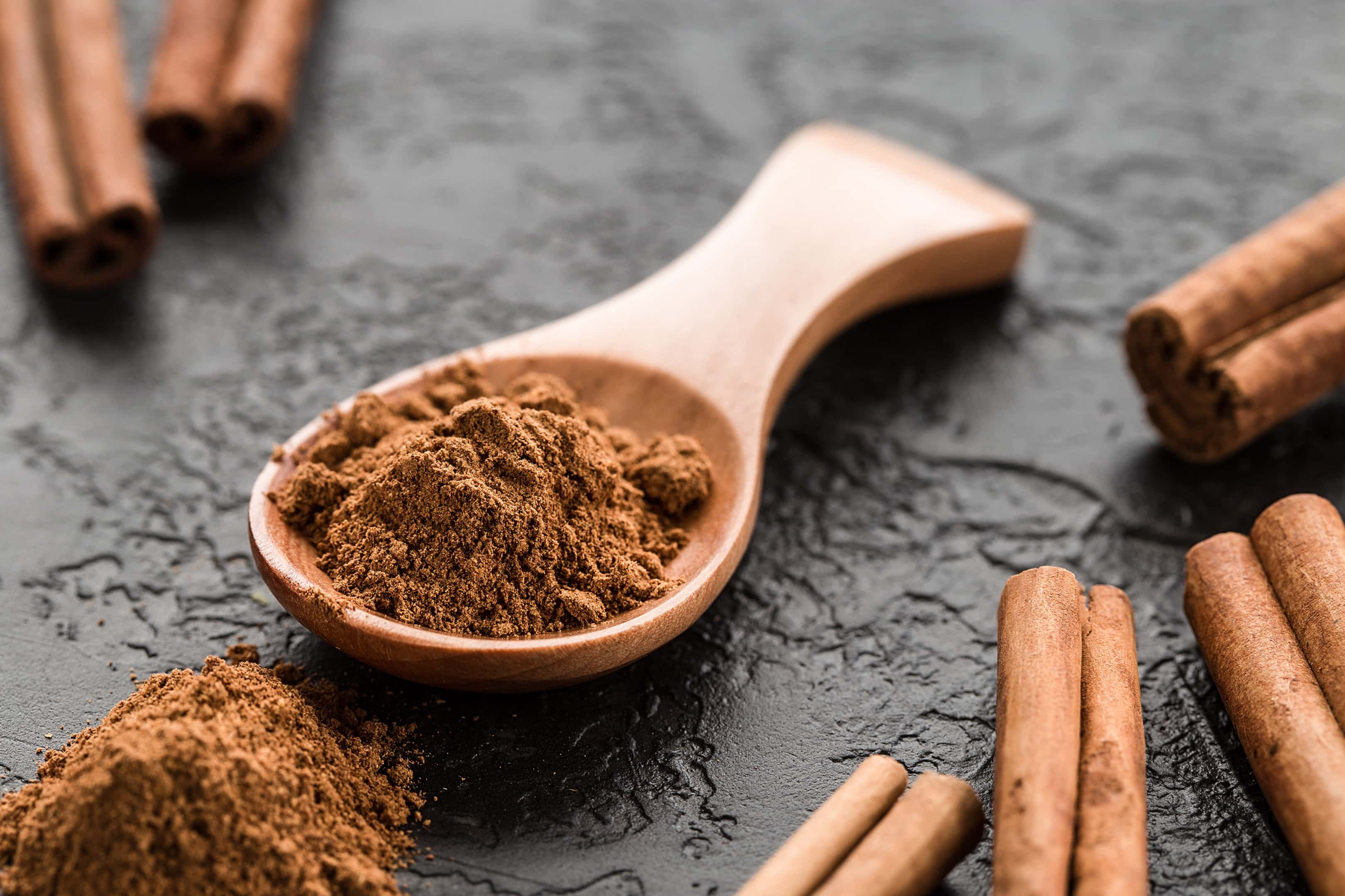 Ground cinnamon powder in wooden spoon