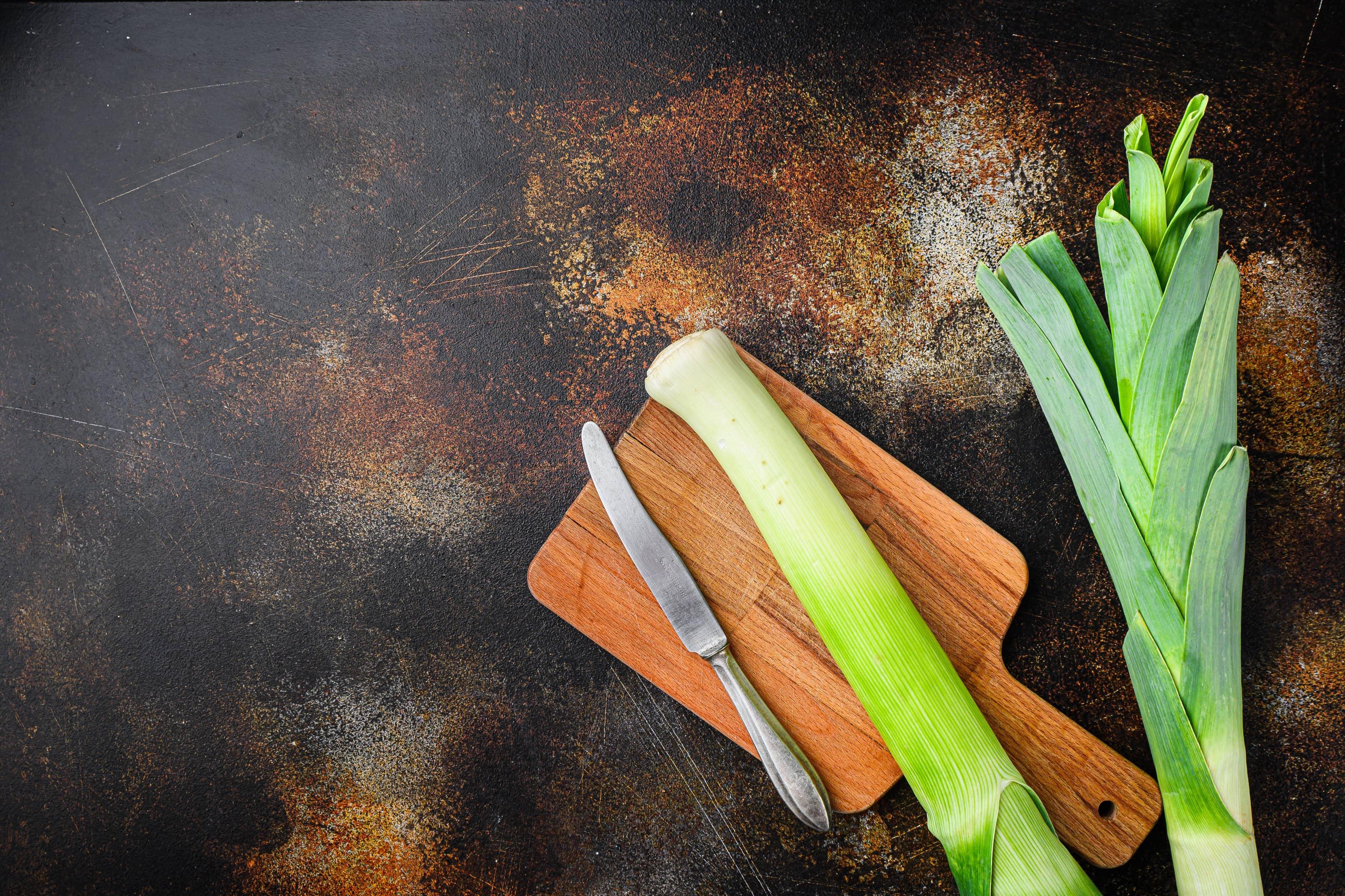 Leek stalks on wooden cutting board