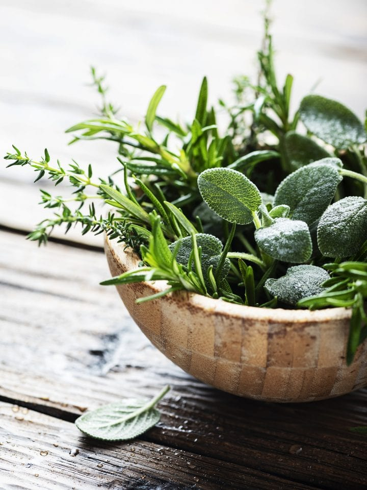 Mix of fresh herbs in wooden bowl
