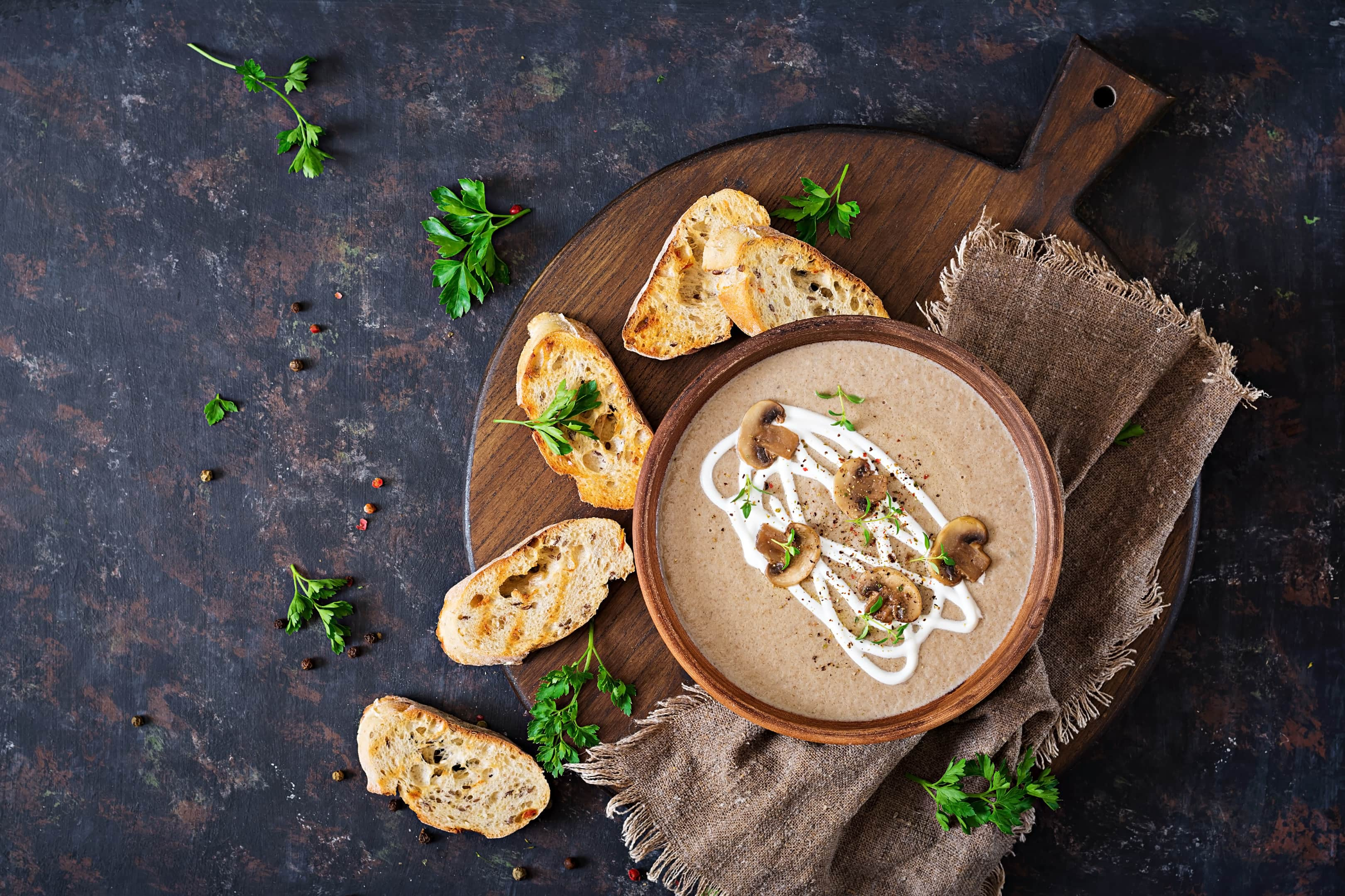 Mushroom cream puree in ceramic bowl on wooden board
