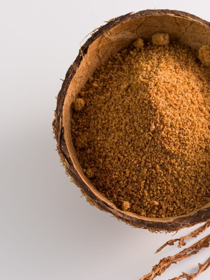 Natural granulated coconut sugar in coconut shell on white background
