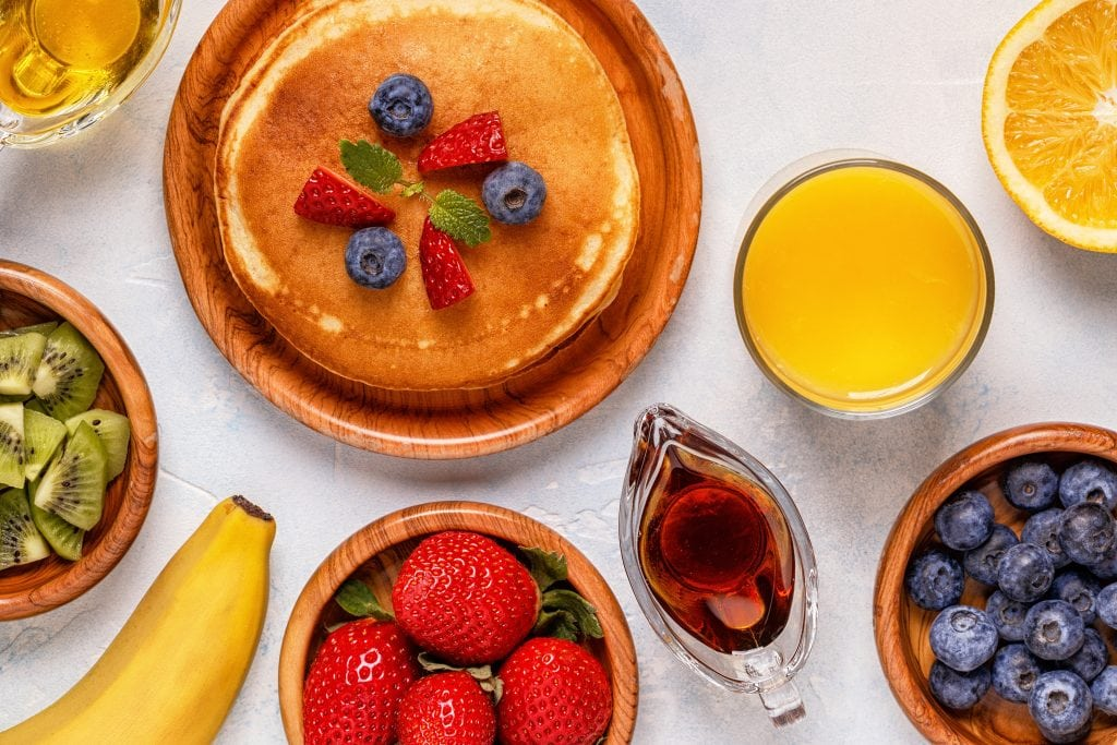 Pancakes with fruit and maple syrup top view