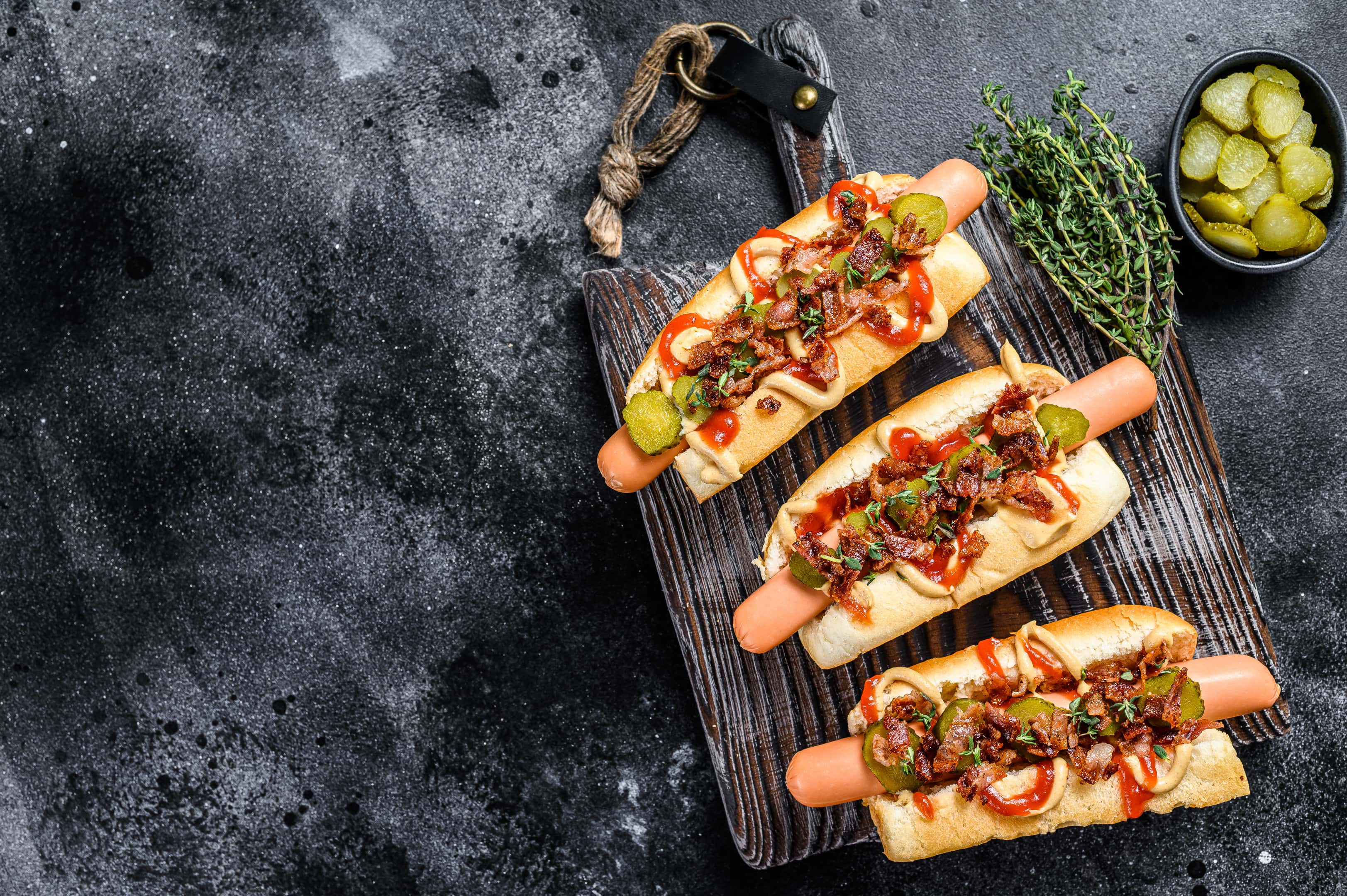Processed hot dogs with different toppings on dark wooden background