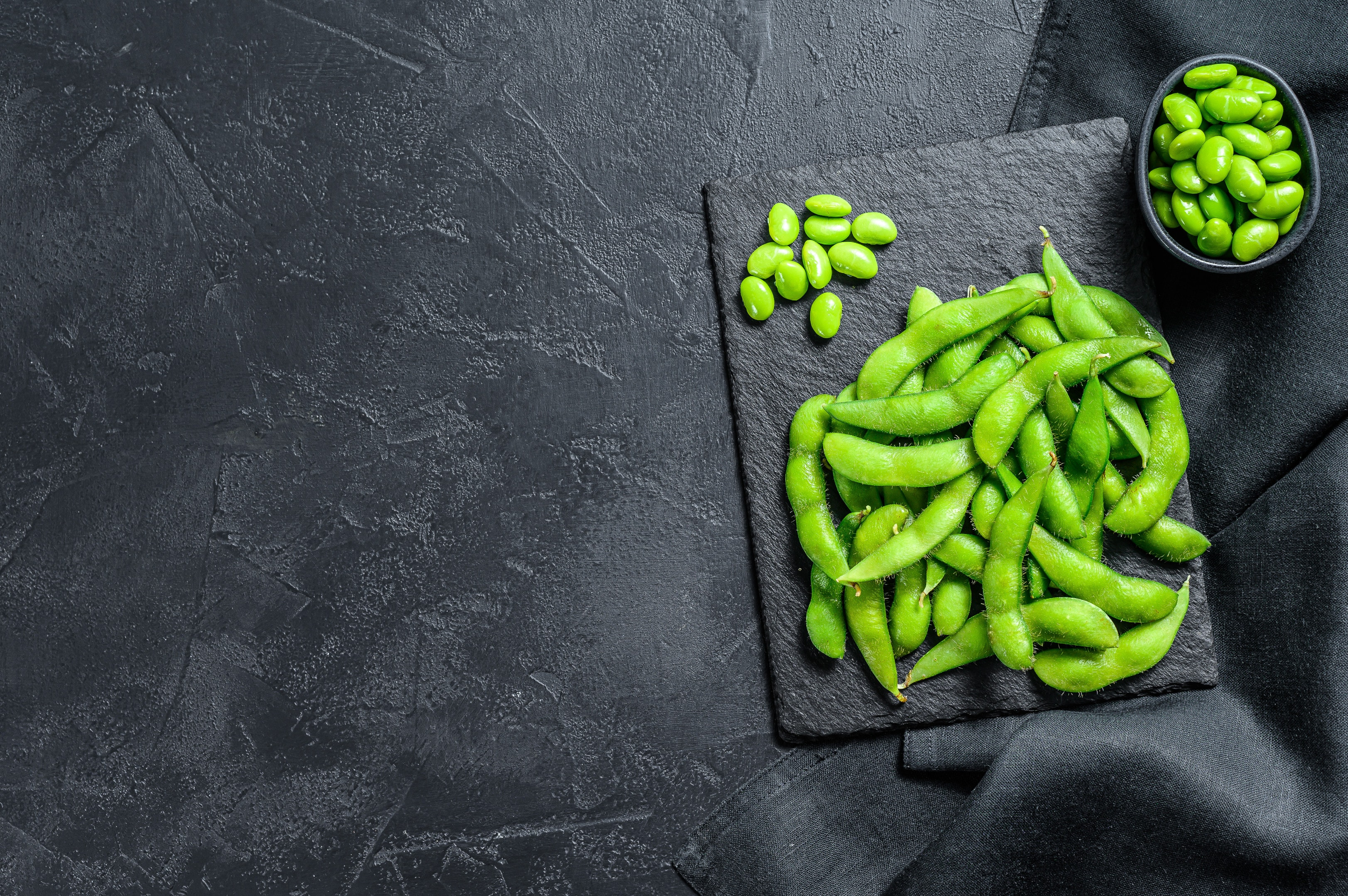 Raw green edamame soybeans on black stone plate
