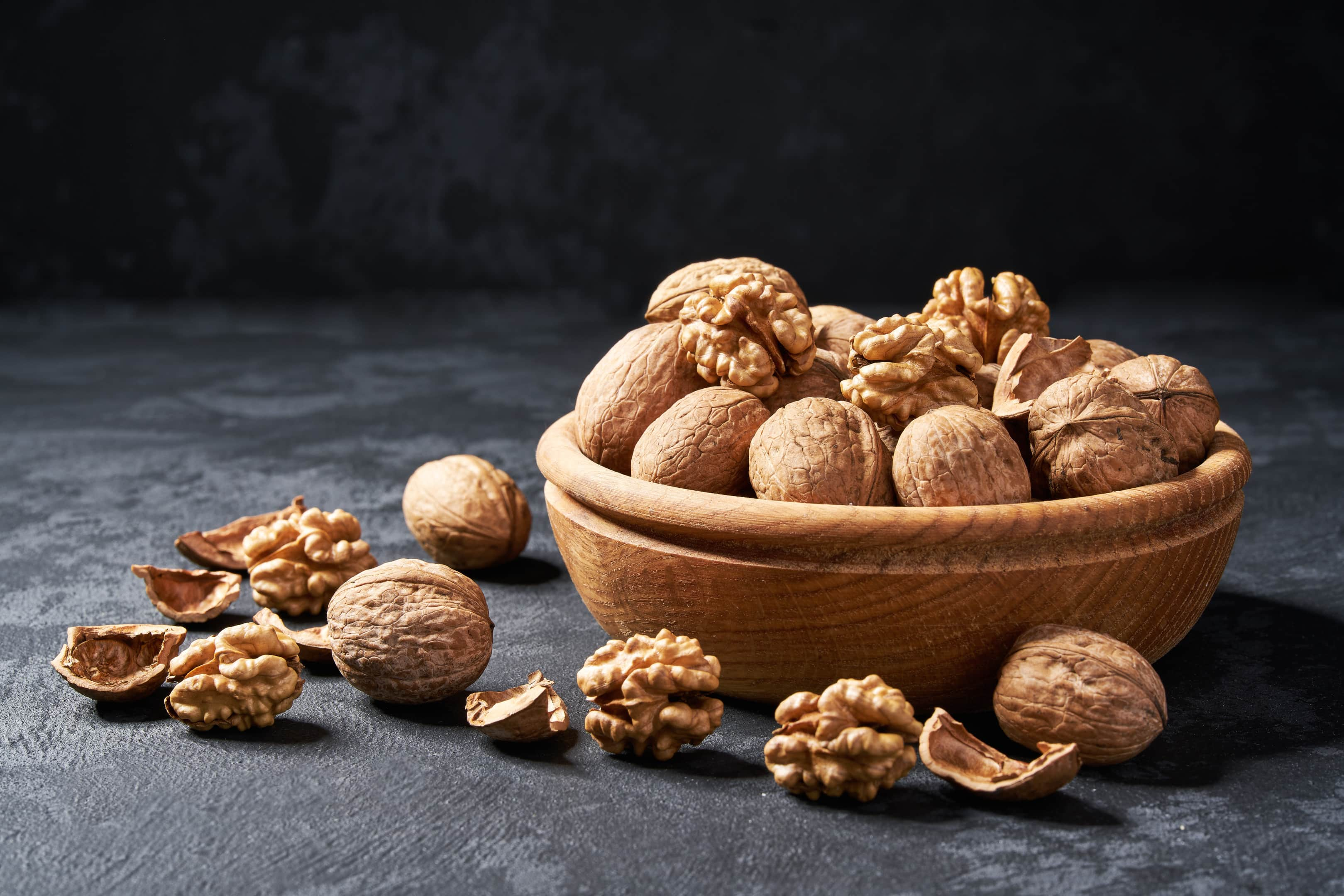 Raw walnuts in wooden bowl on dark table