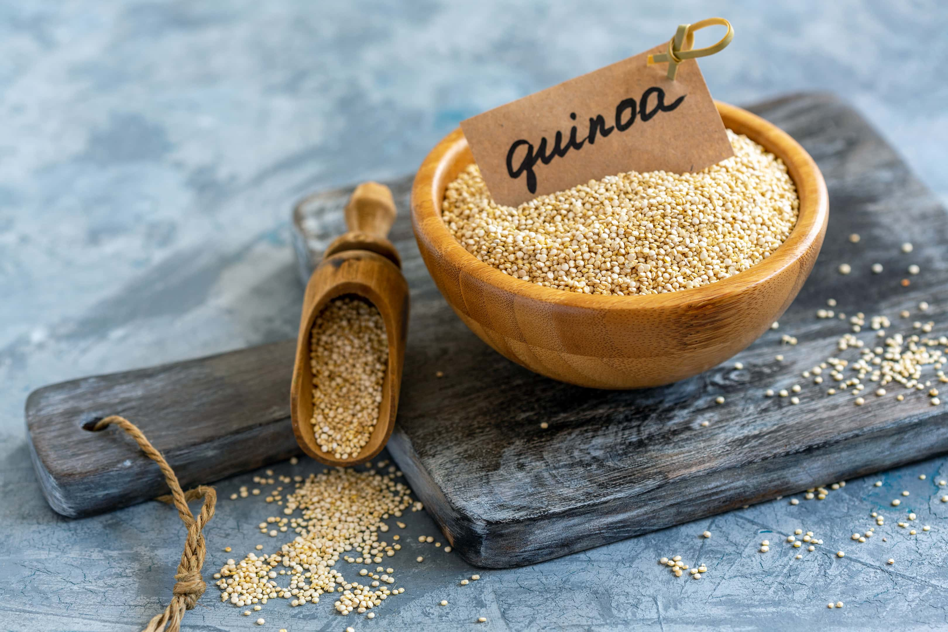 Raw white quinoa in wooden bowl on wooden board