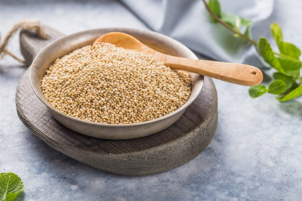 Raw white quinoa seeds in plate with wooden spoon