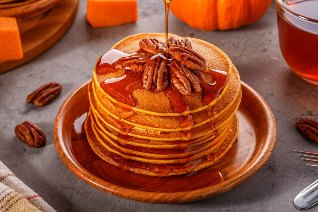 Stack pumpkin pancakes with pecans and maple syrup