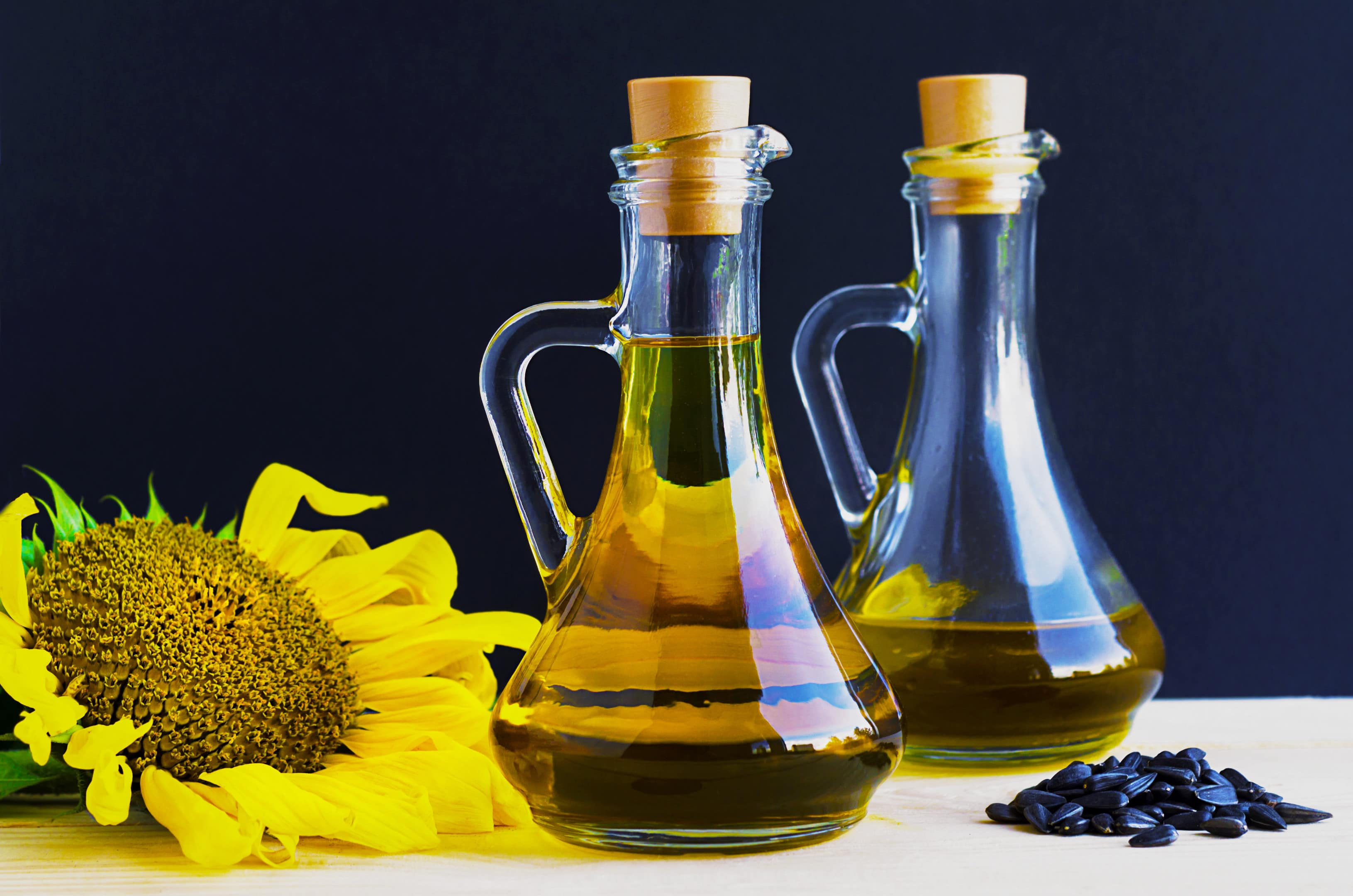 Sunflower oil glass jugs with sunflower and sunflower seeds on table