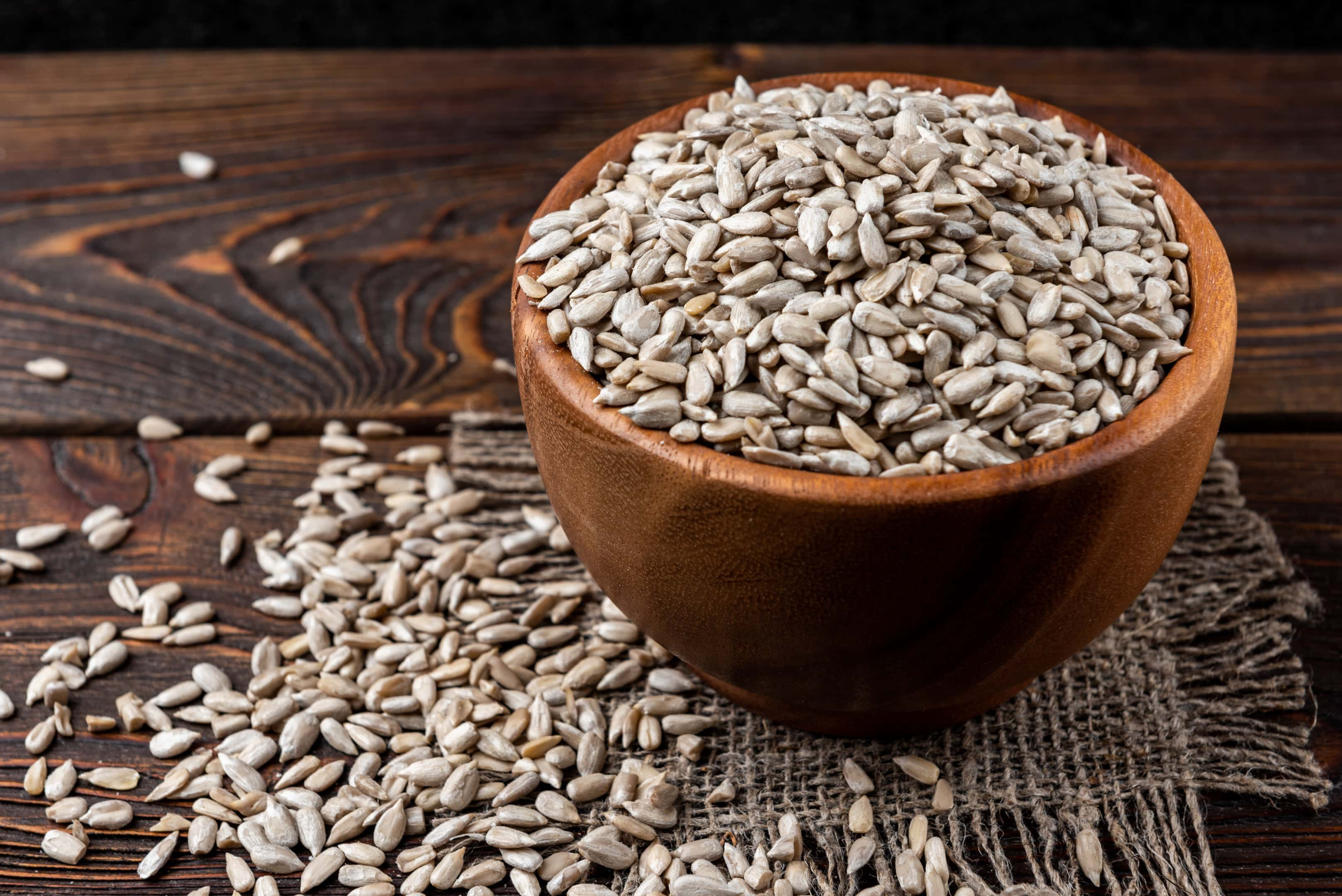 Sunflower seeds in wooden bowl on wooden table