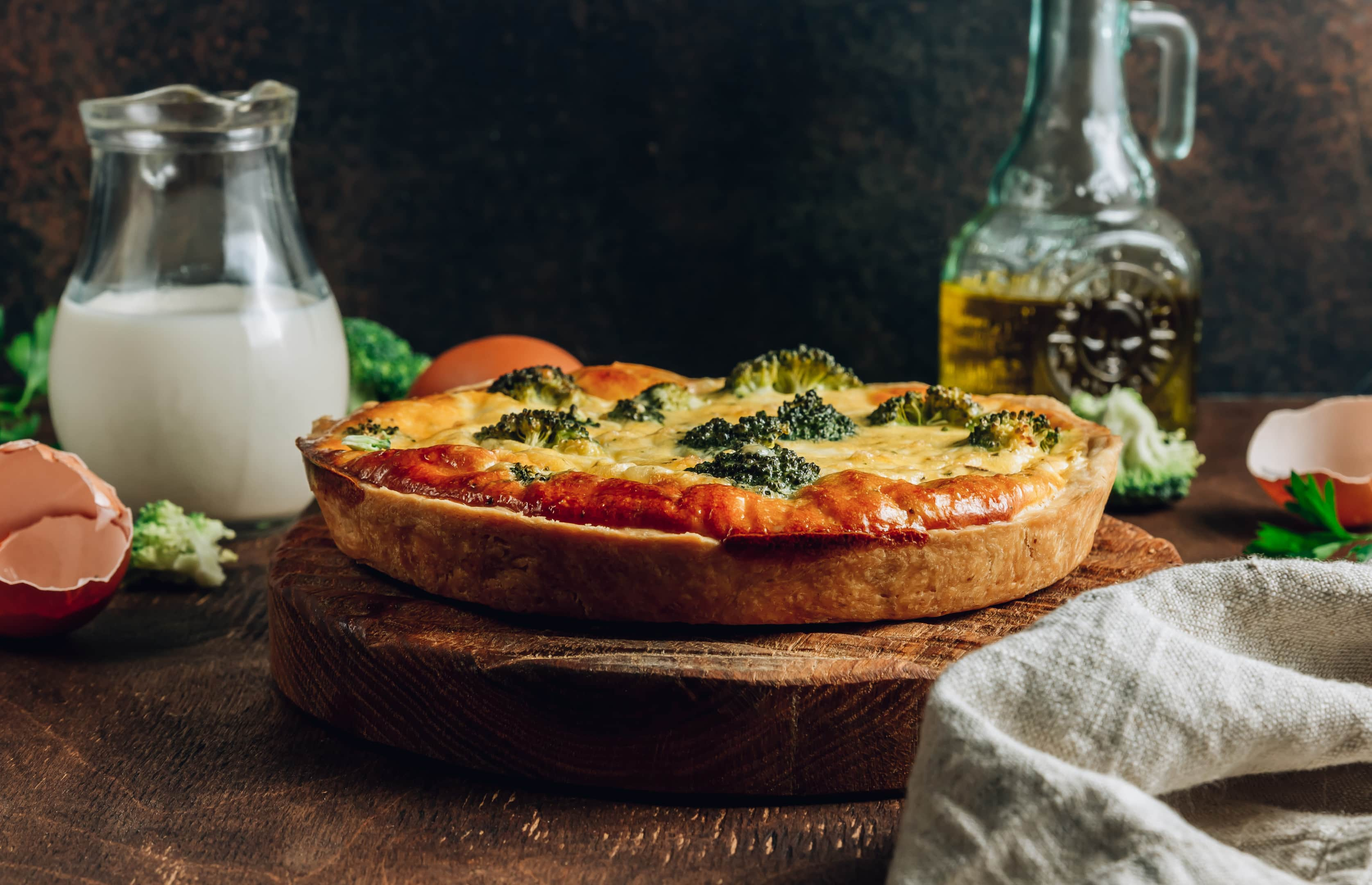 Traditional vegetable quiche with broccoli on wooden board