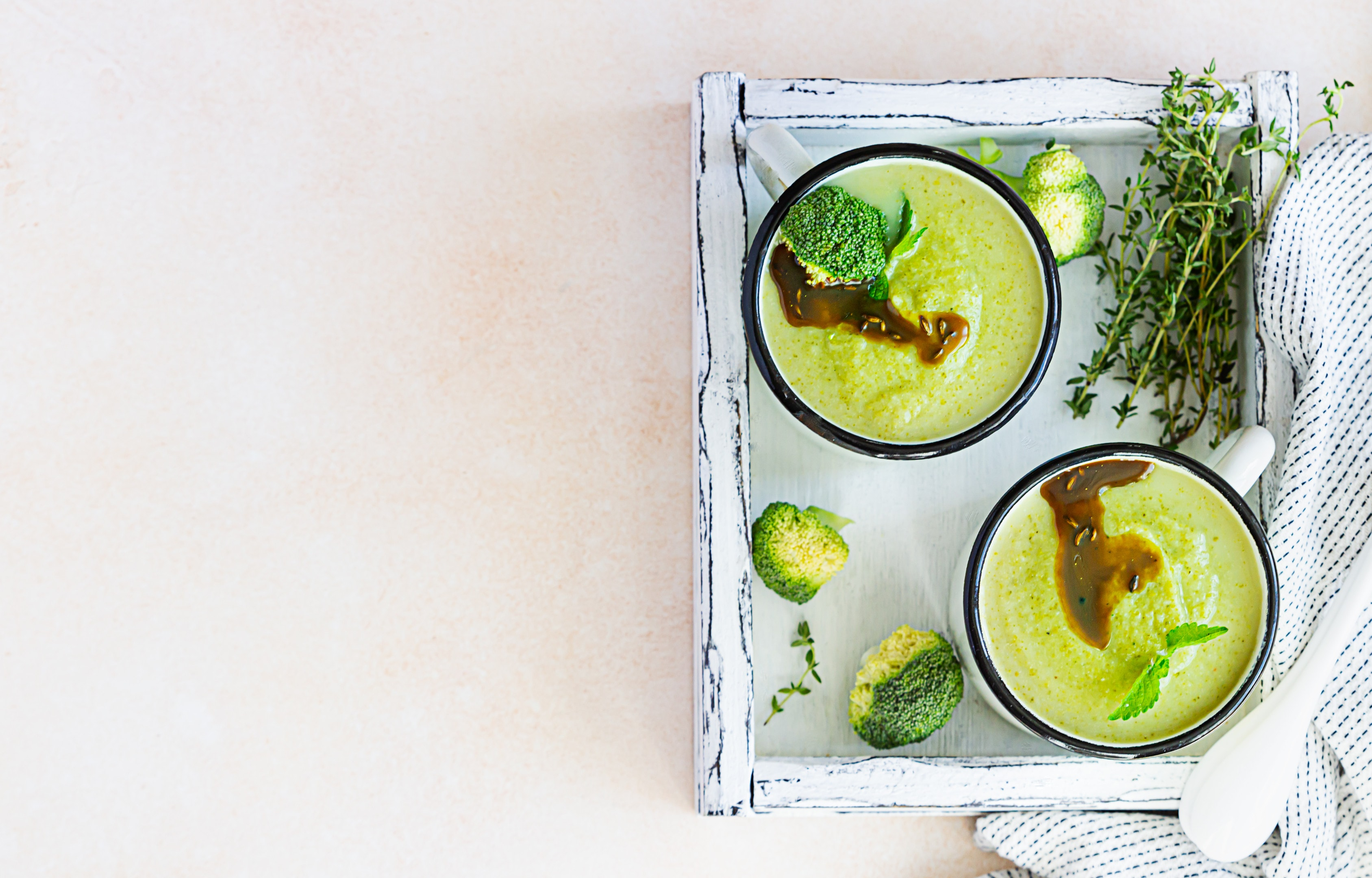Two enamel mugs with healthy vegan broccoli soup puree