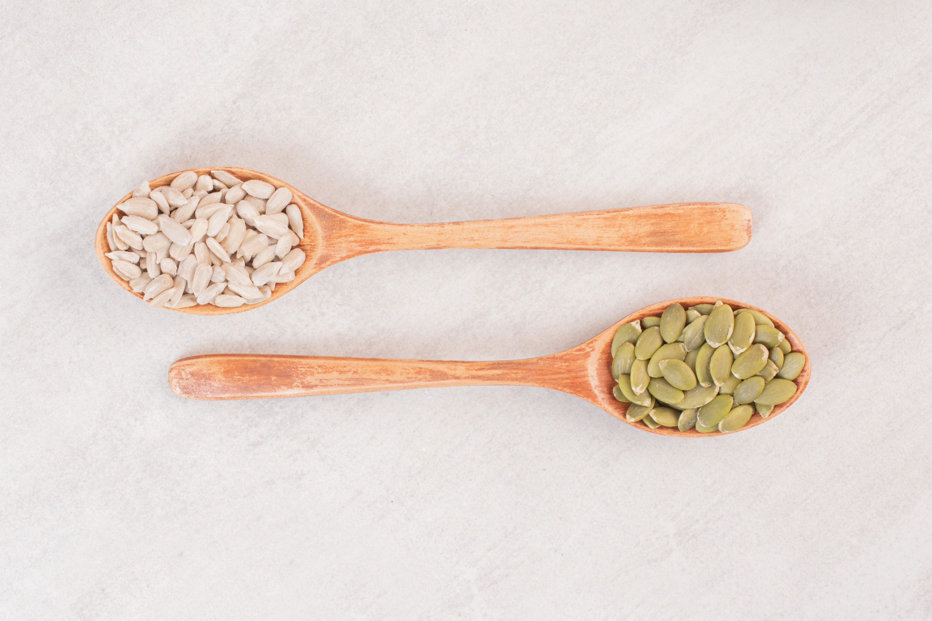 Two wooden spoon with sunflower and pumpkin seeds on white surface