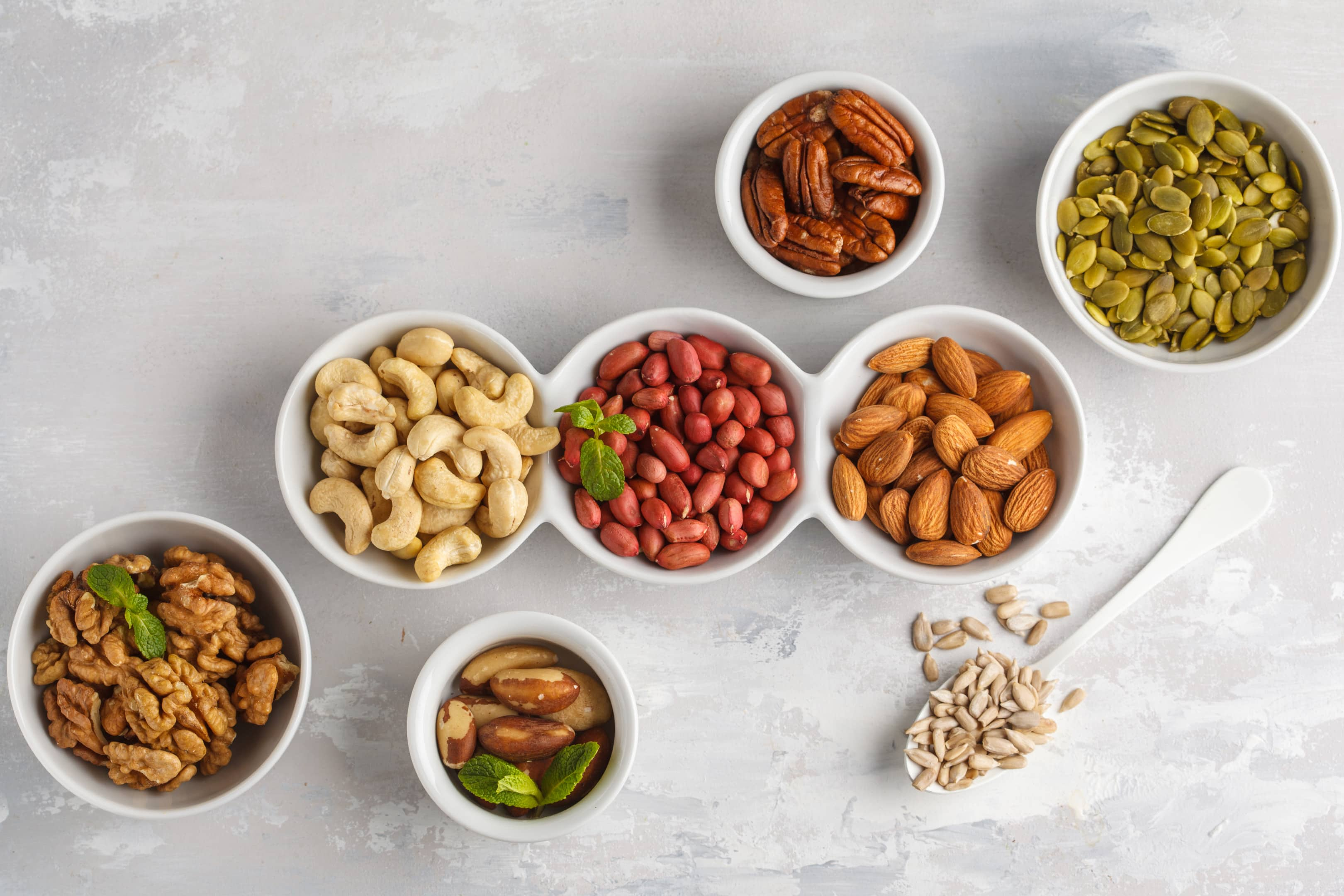 Variety of nuts and seeds in white bowls on gray background