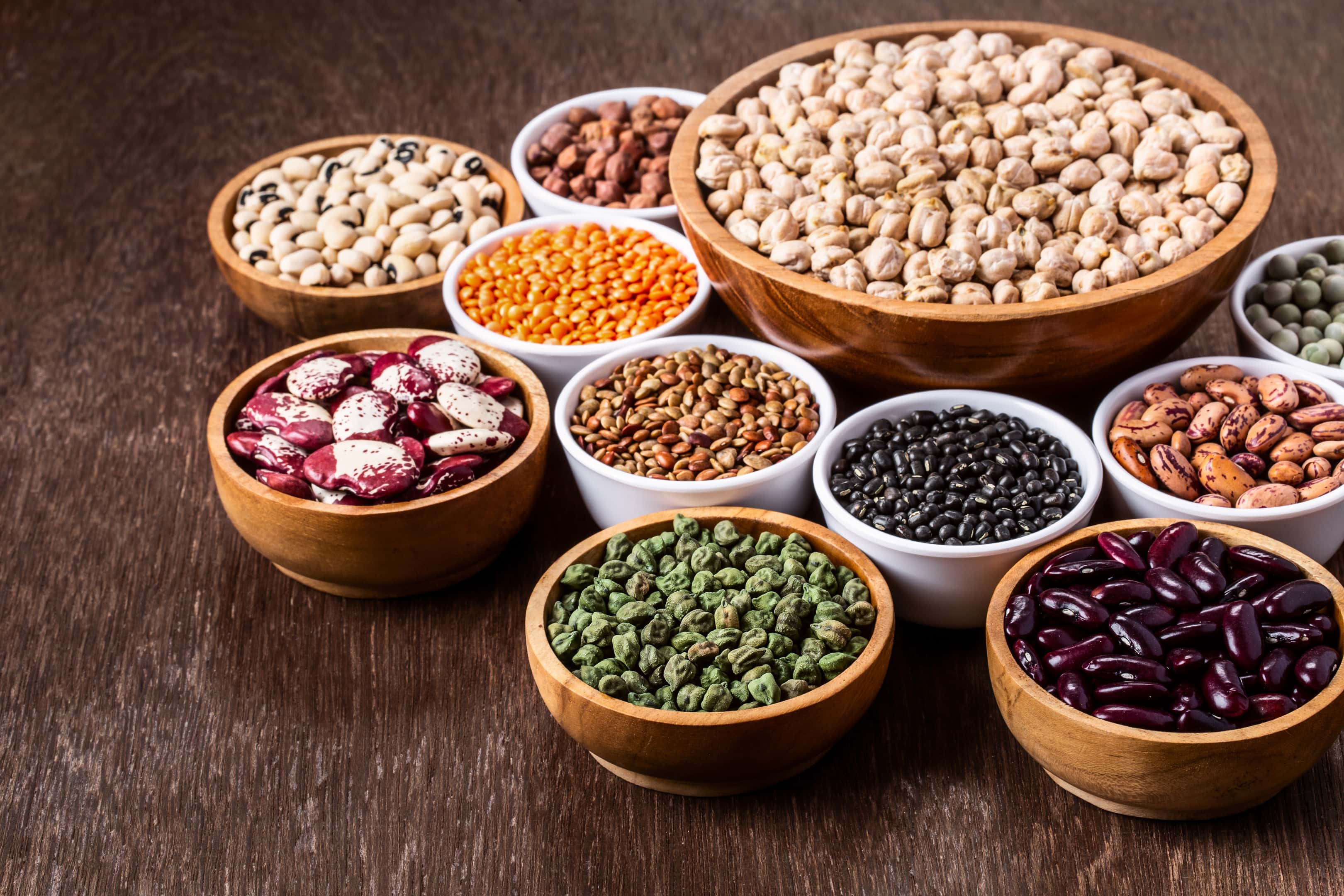 Various assortment of legumes in bowls wooden on wooden table