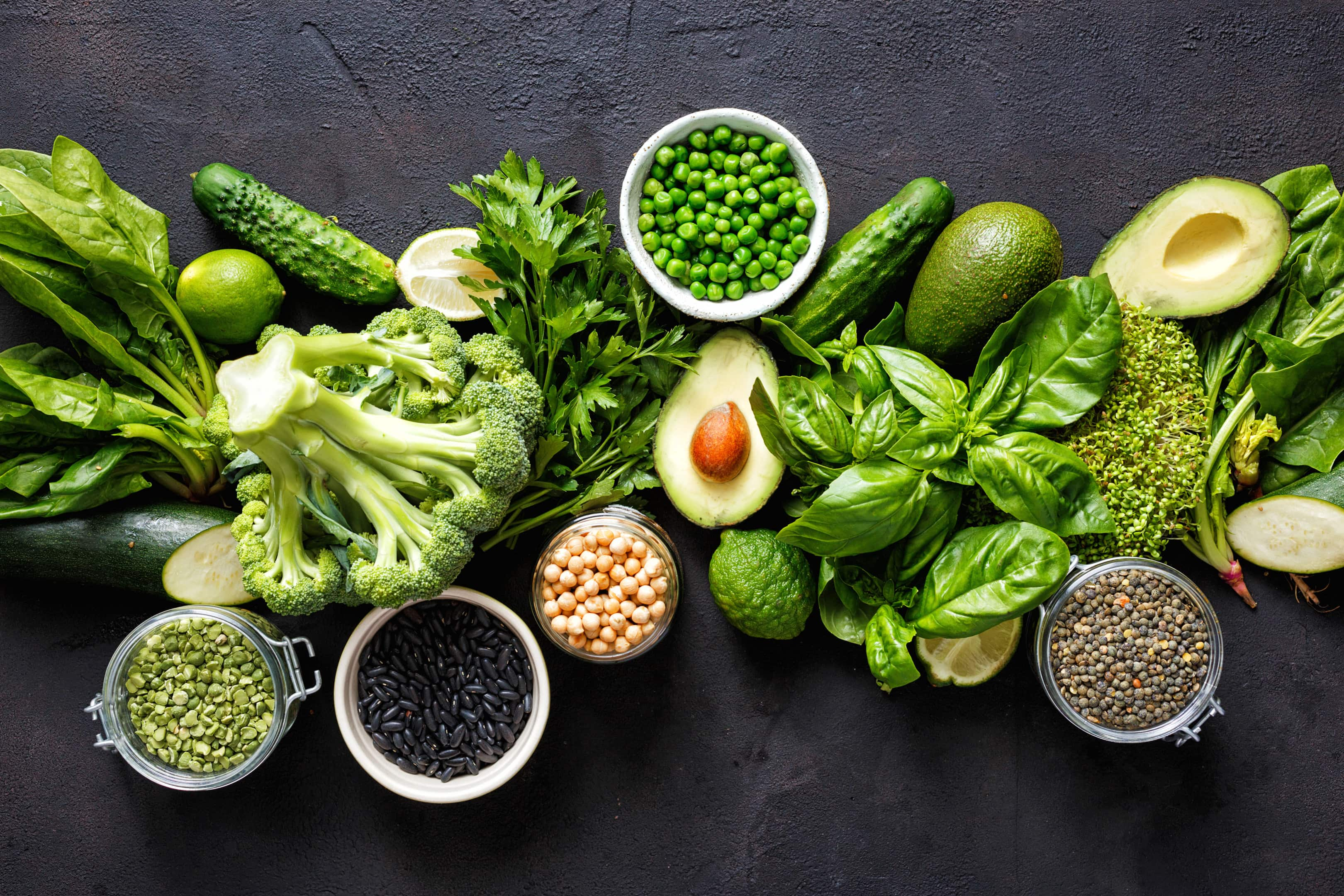 Various leafy green vegetables on dark background