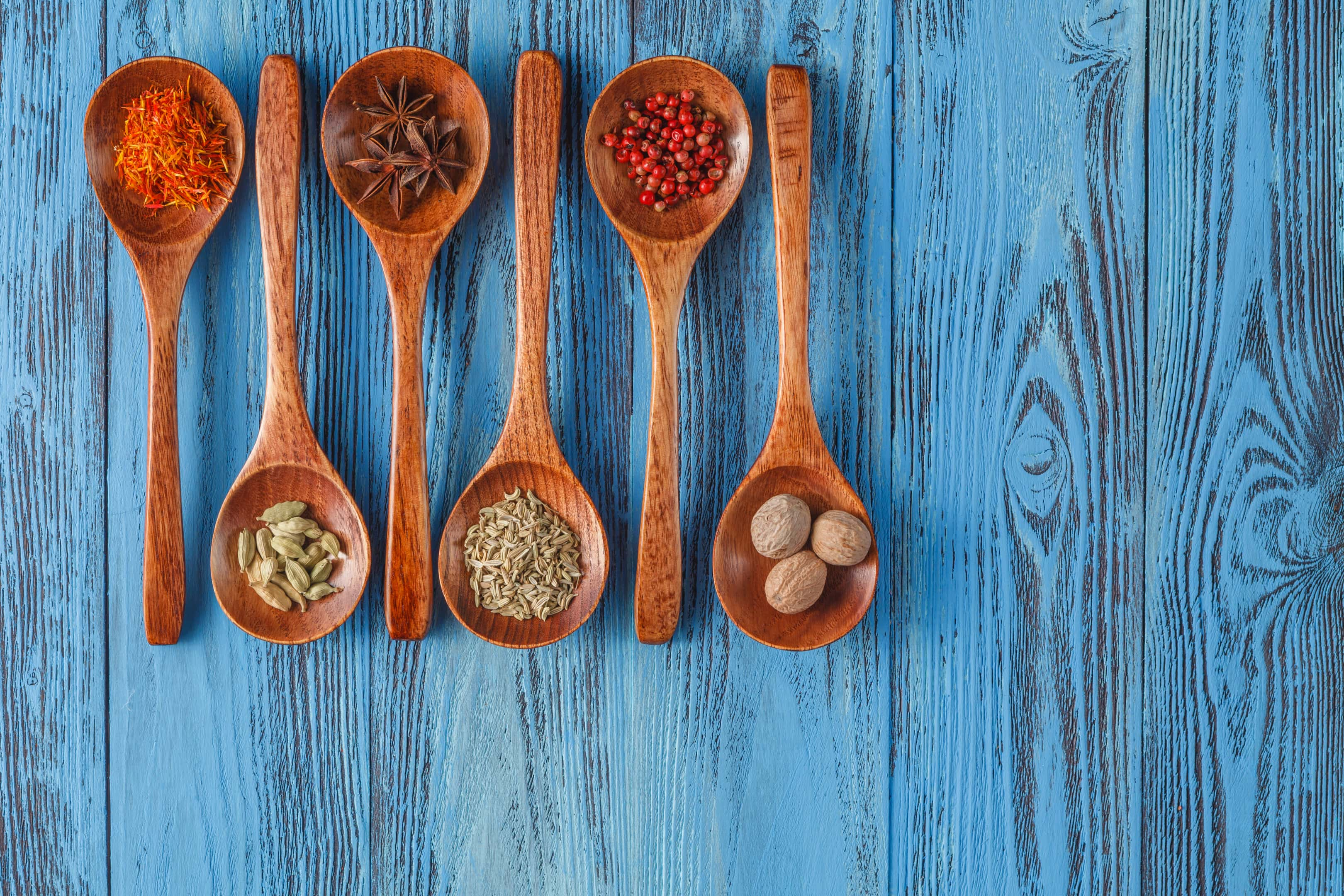 Various spice herbs in wooden spoons on wooden table