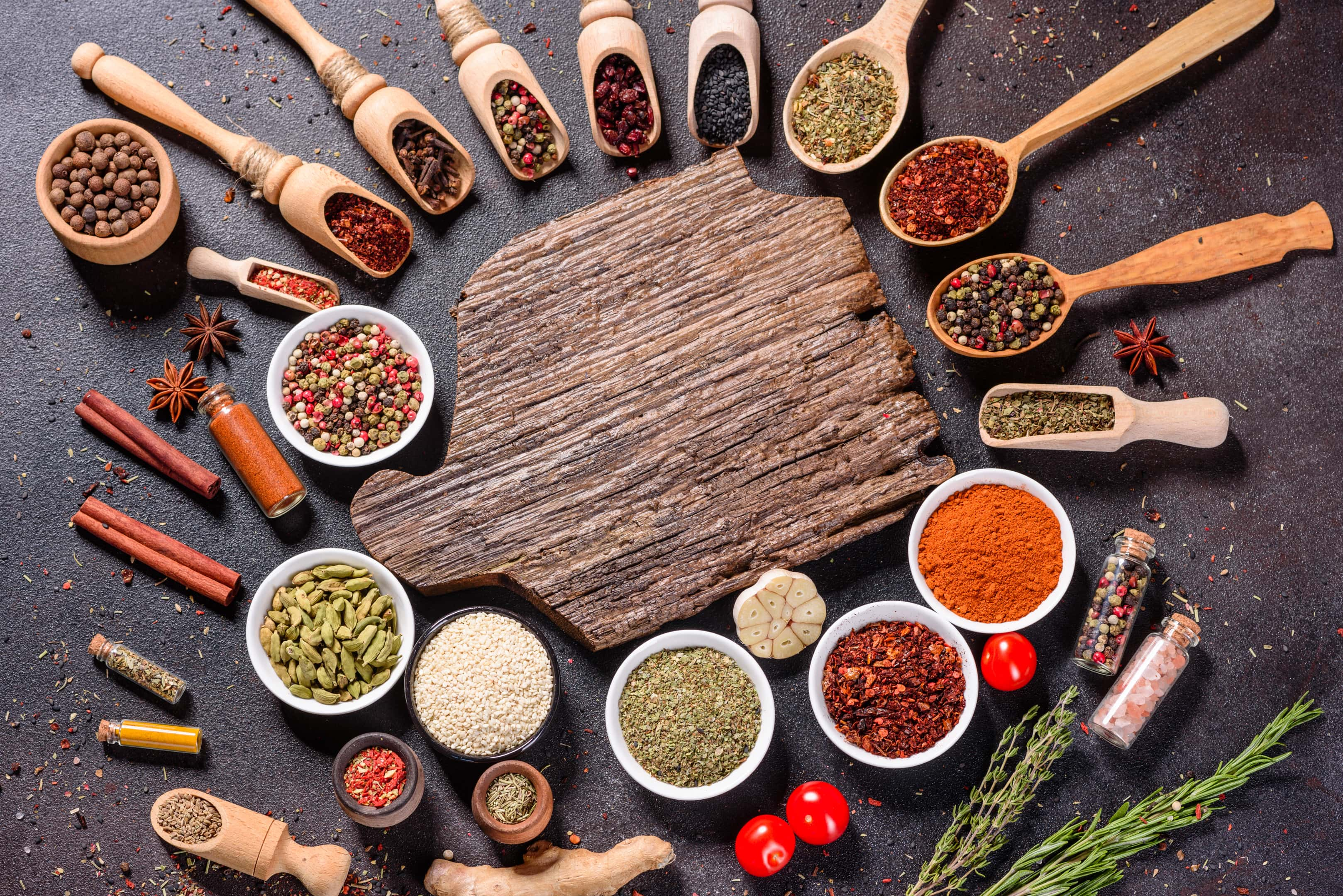 Various spices and herbs in wooden spoons surrounding wooden board