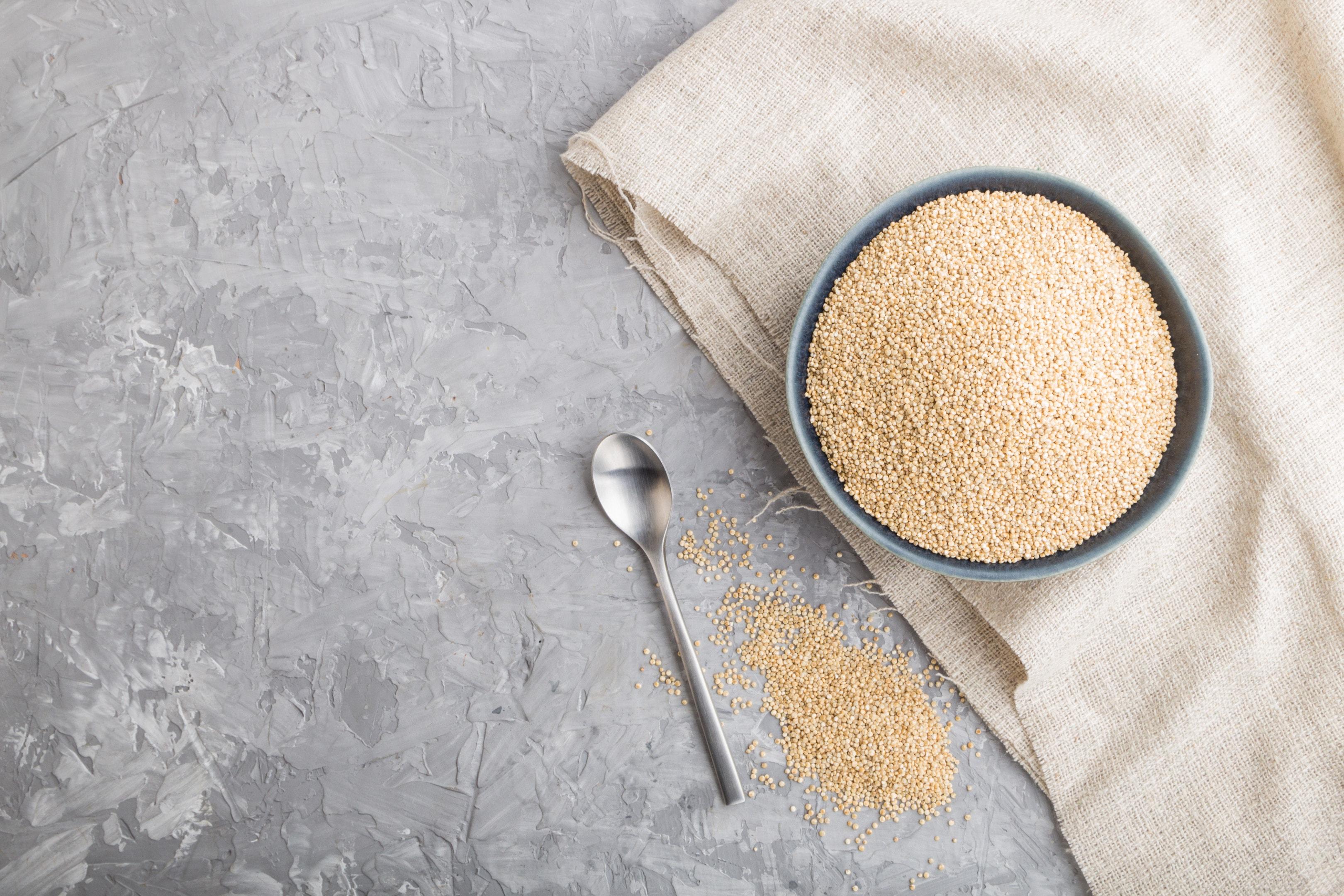 White quinoa seeds in blue ceramic bowl