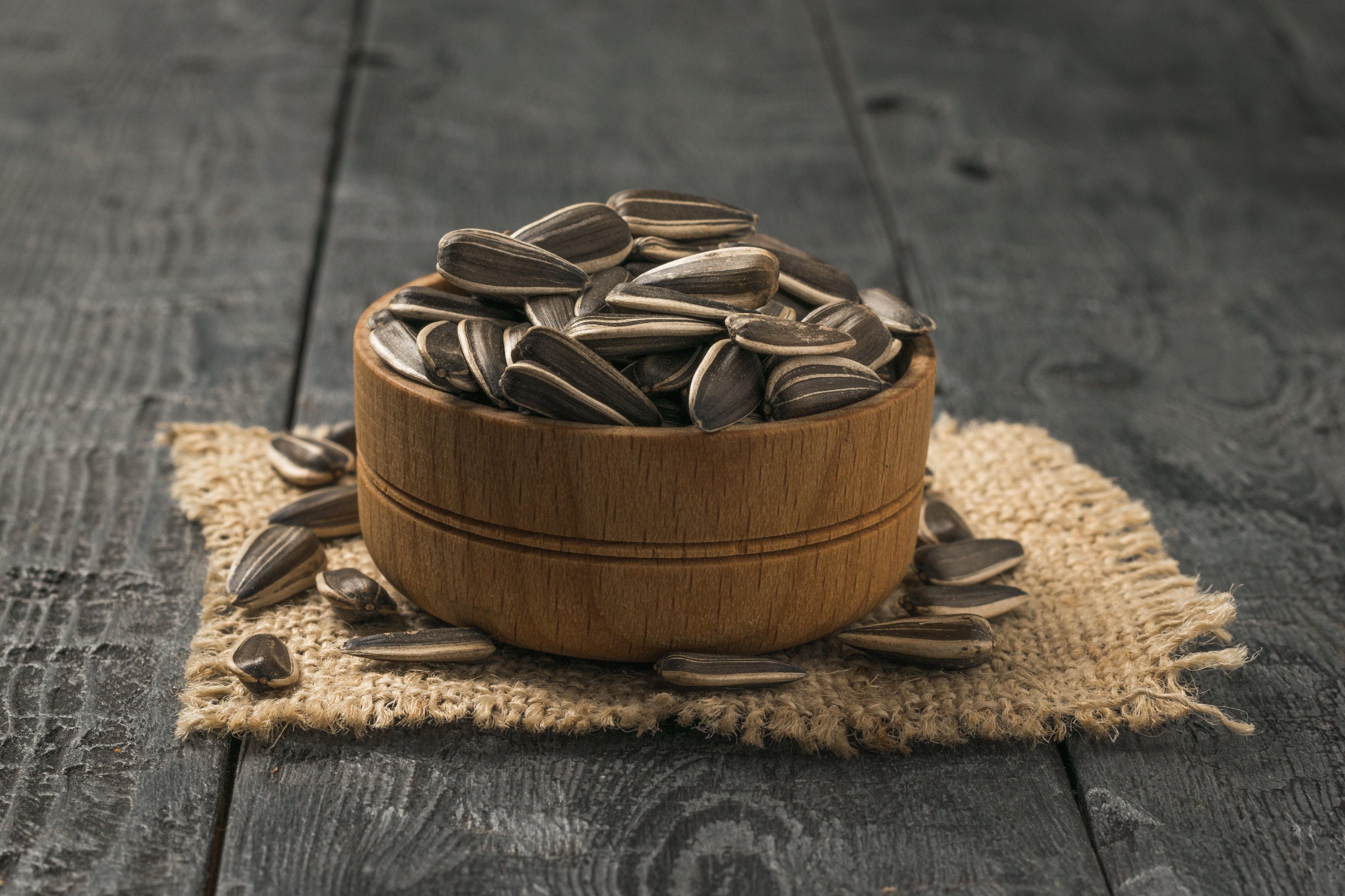 Wooden bowl with sunflower seeds on wooden table