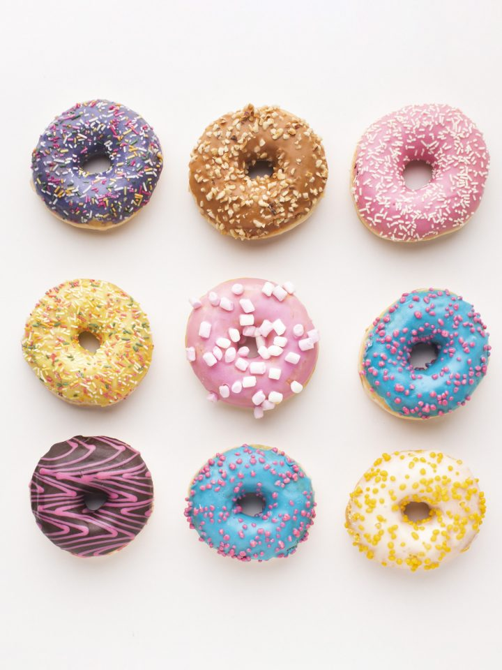 Assorted delicious donuts on white background