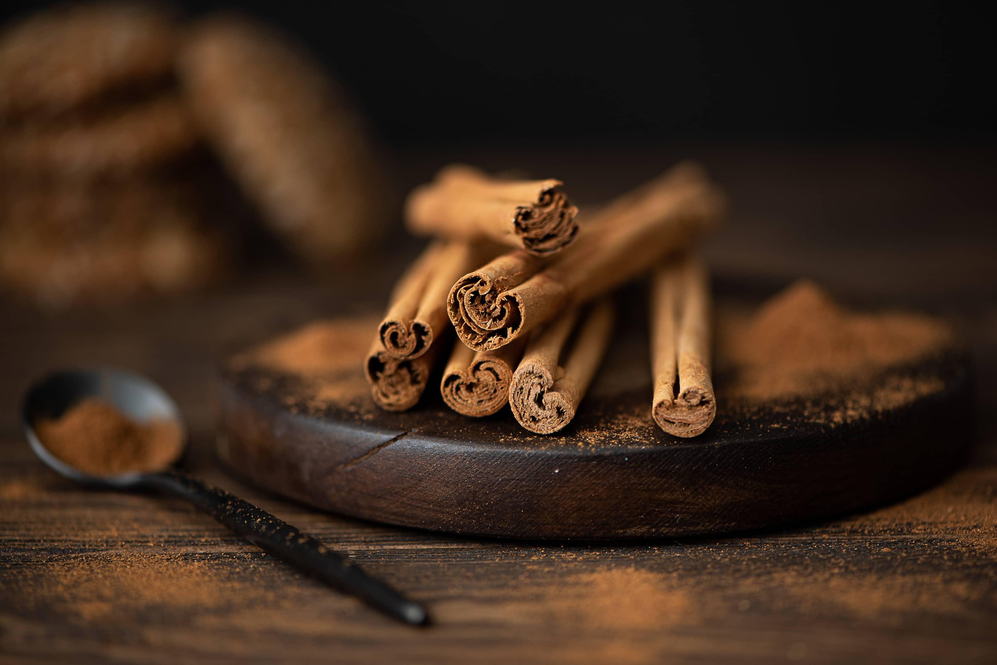 Cinnamon sticks and powder on wooden board