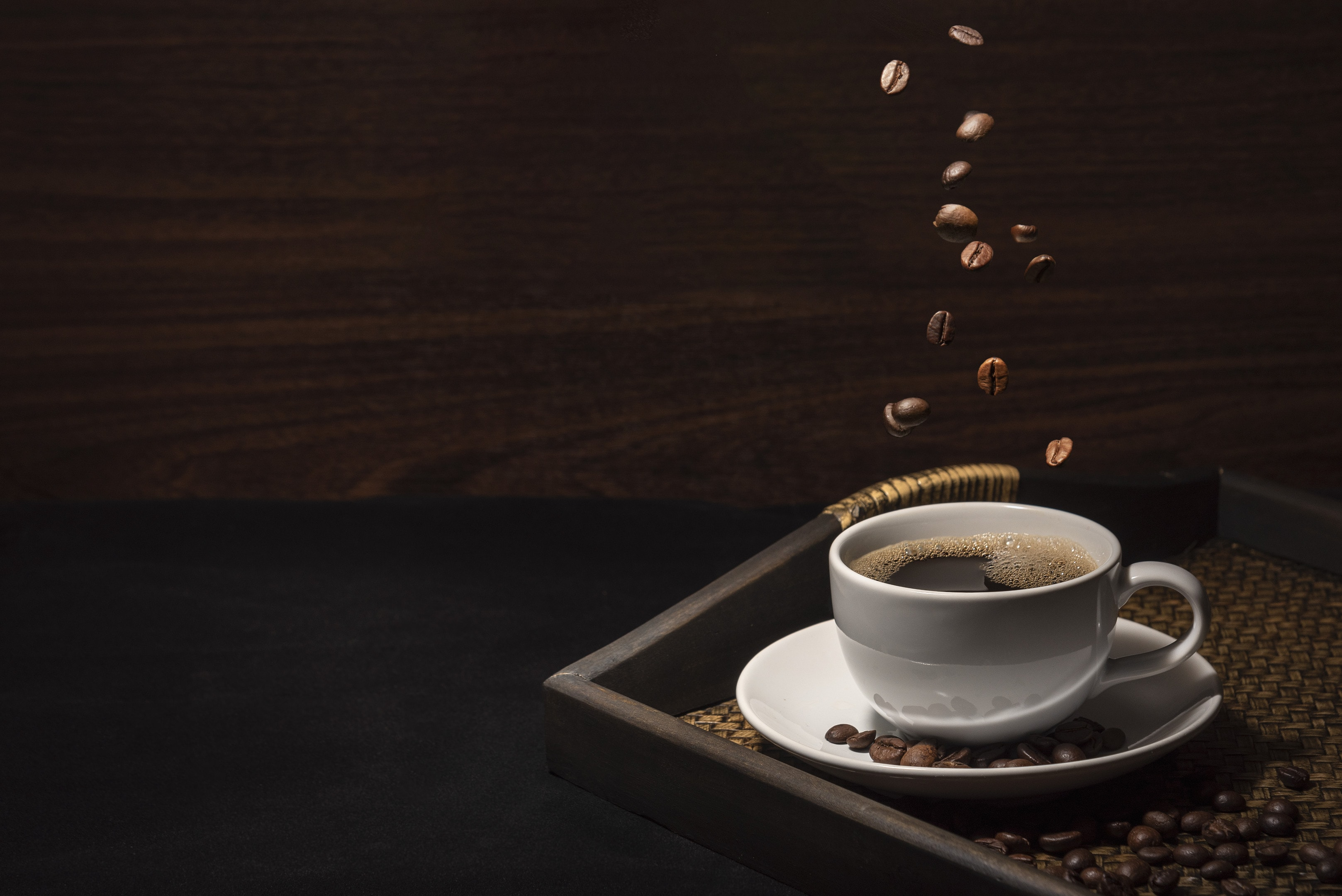 Coffee cup with coffee beans on bamboo tray