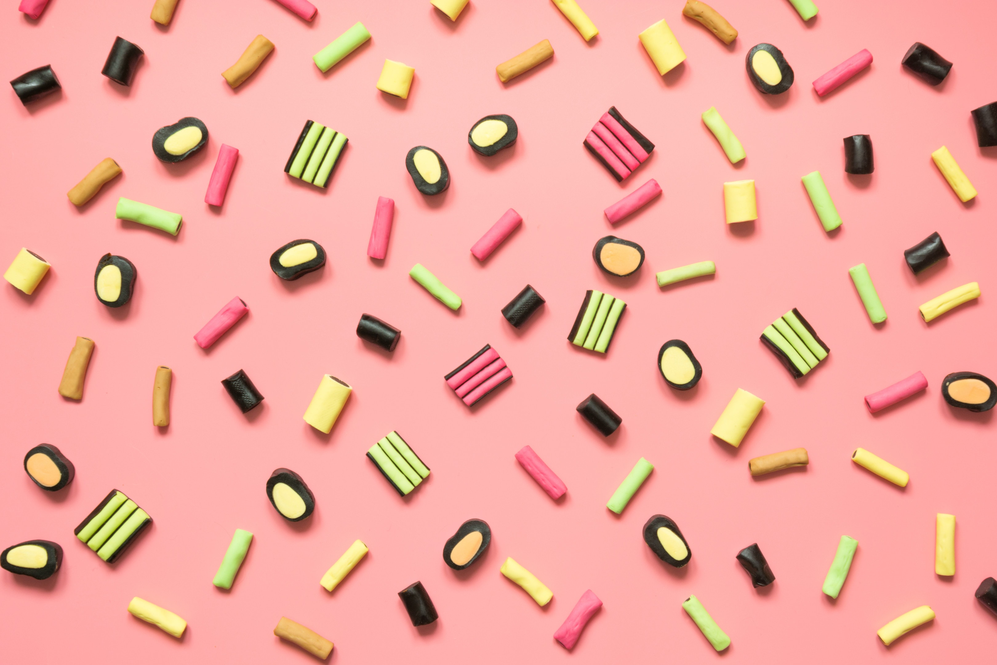 Colorful lollipop and licorice candy assortment on pink background