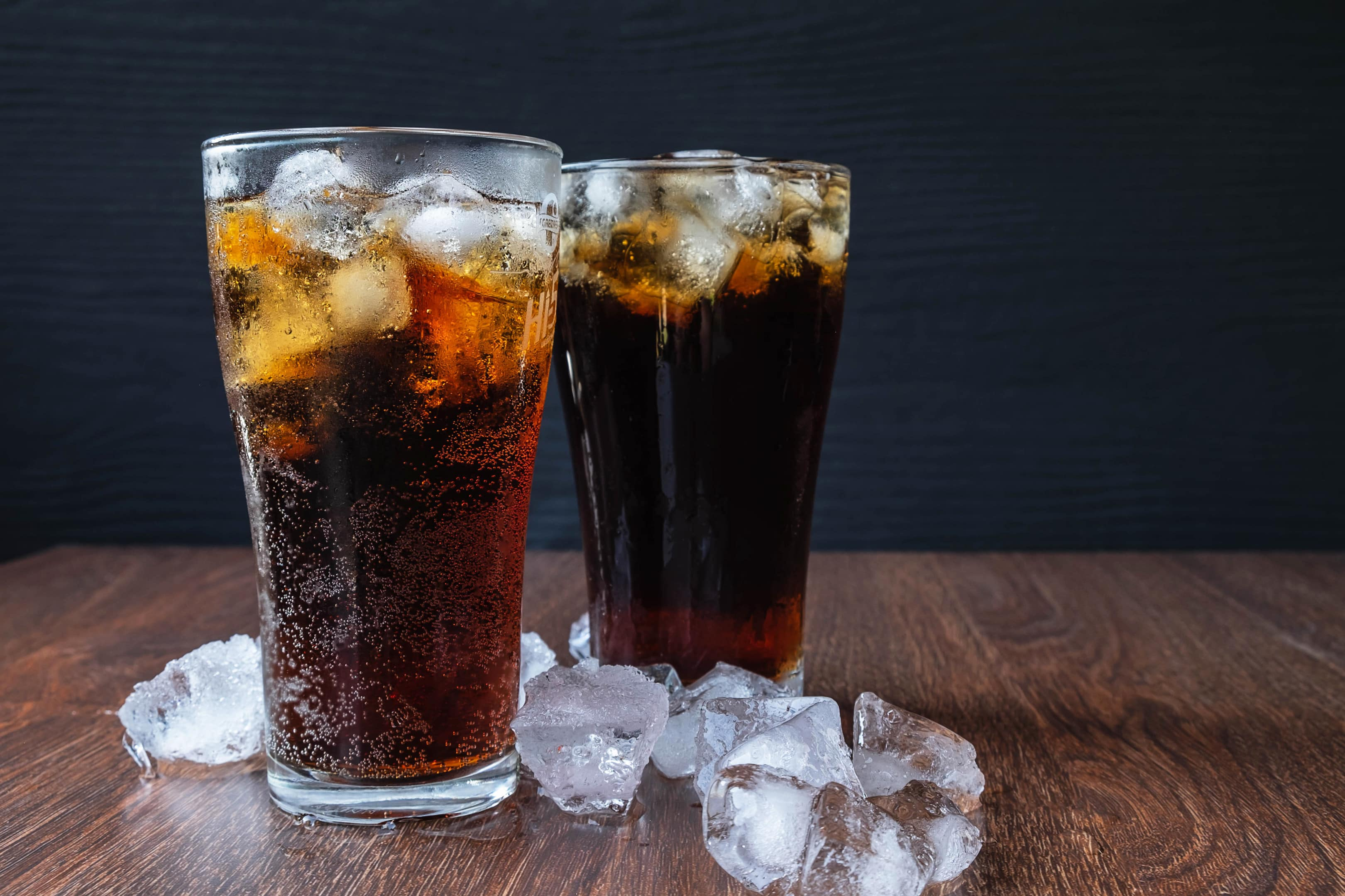 Diet cola soda glass with ice cubes on wooden table