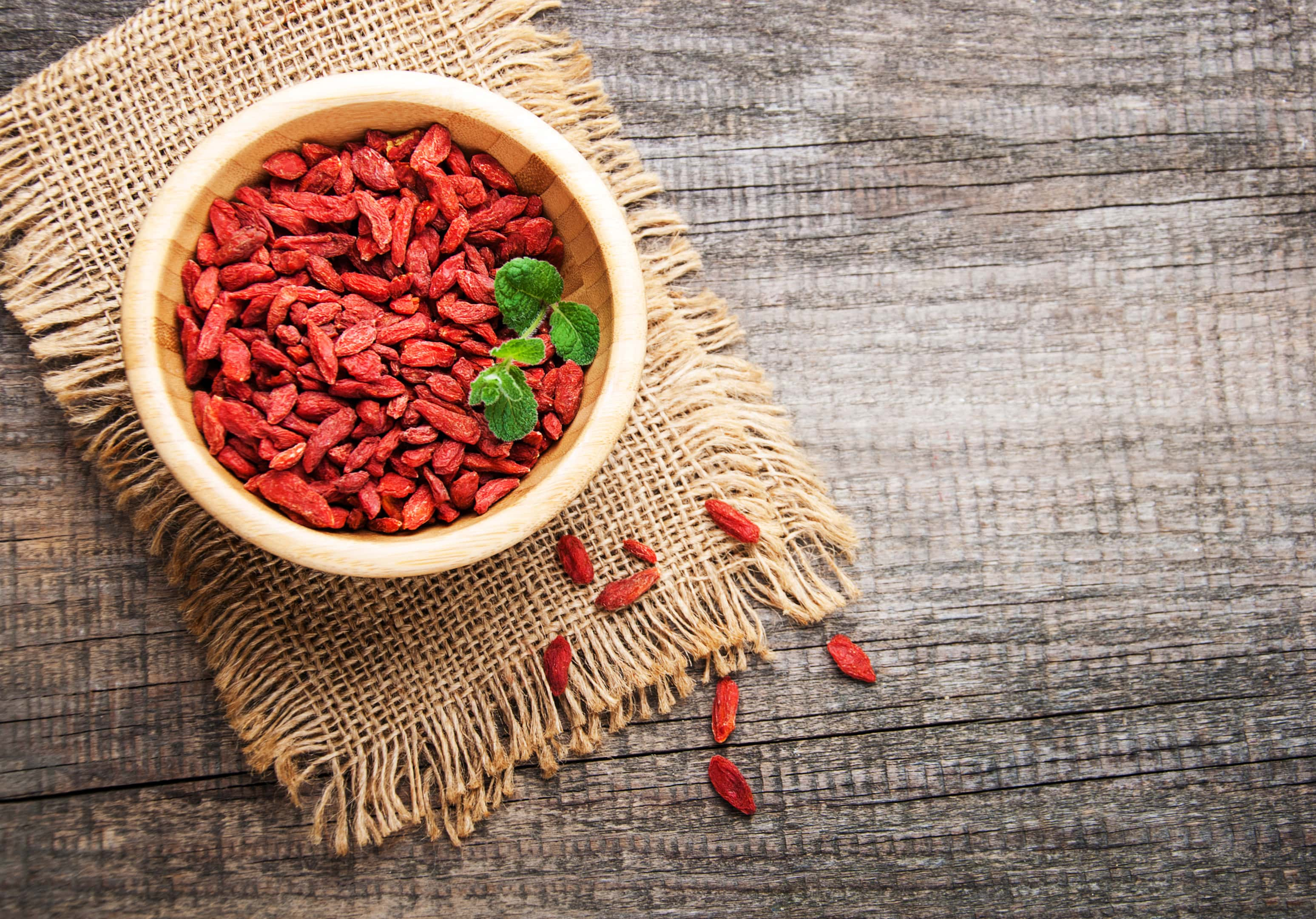 Dry red goji berries in wooden bowl