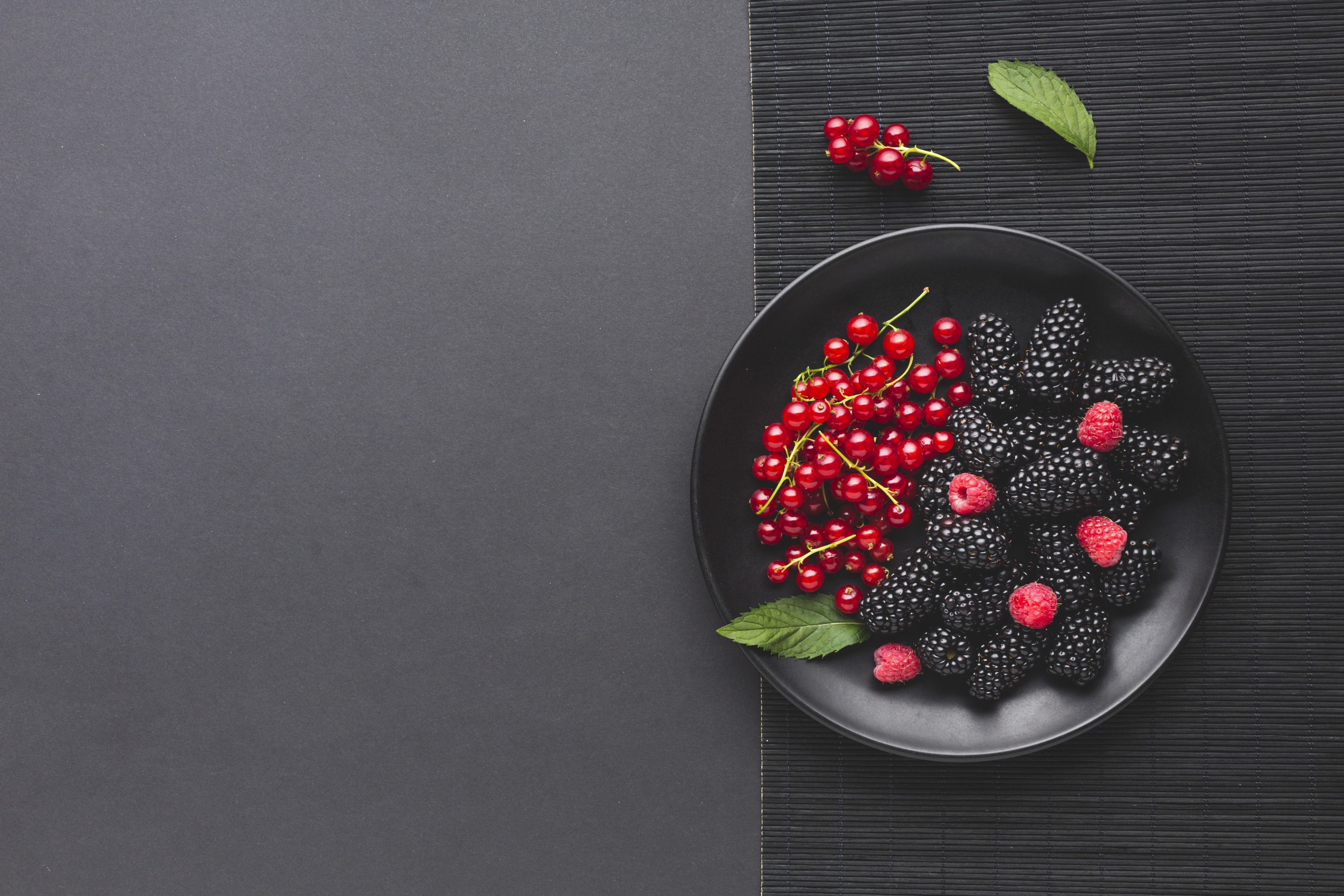 Flat lay plate of fresh berries on wooden table