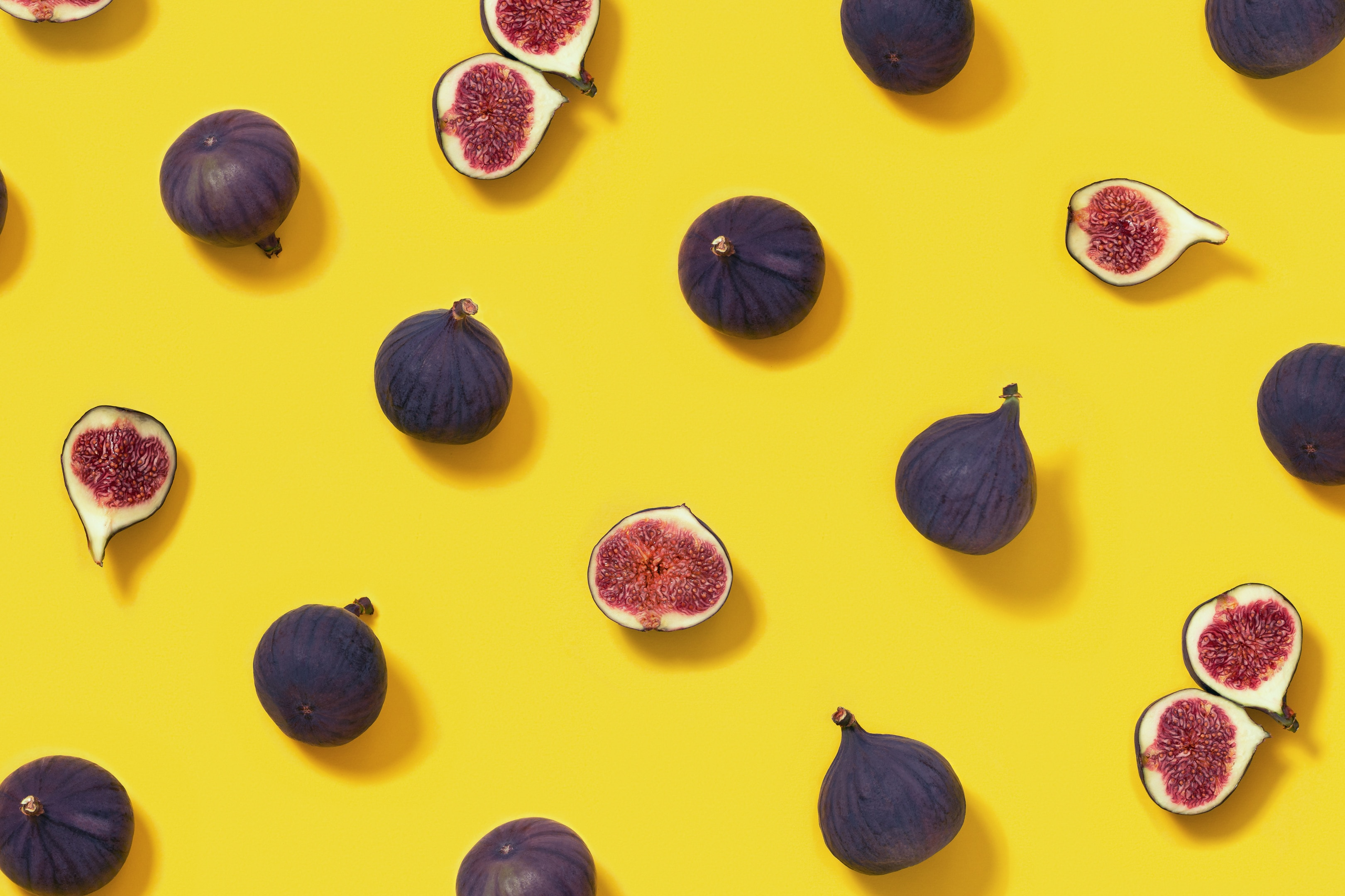 Fresh figs whole and sliced figs on yellow background
