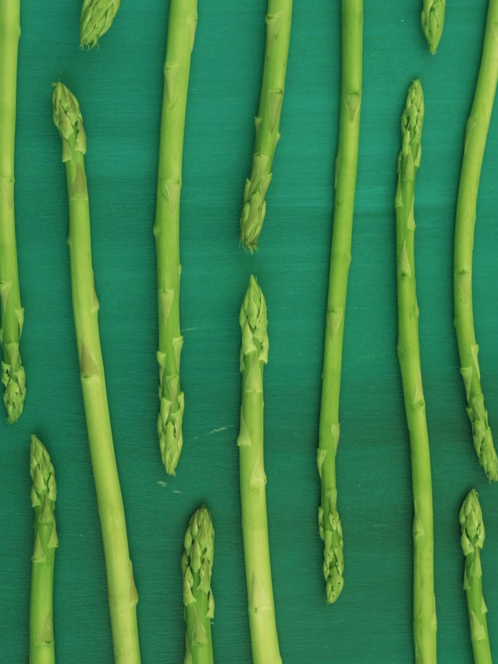 Fresh green asparagus on green background