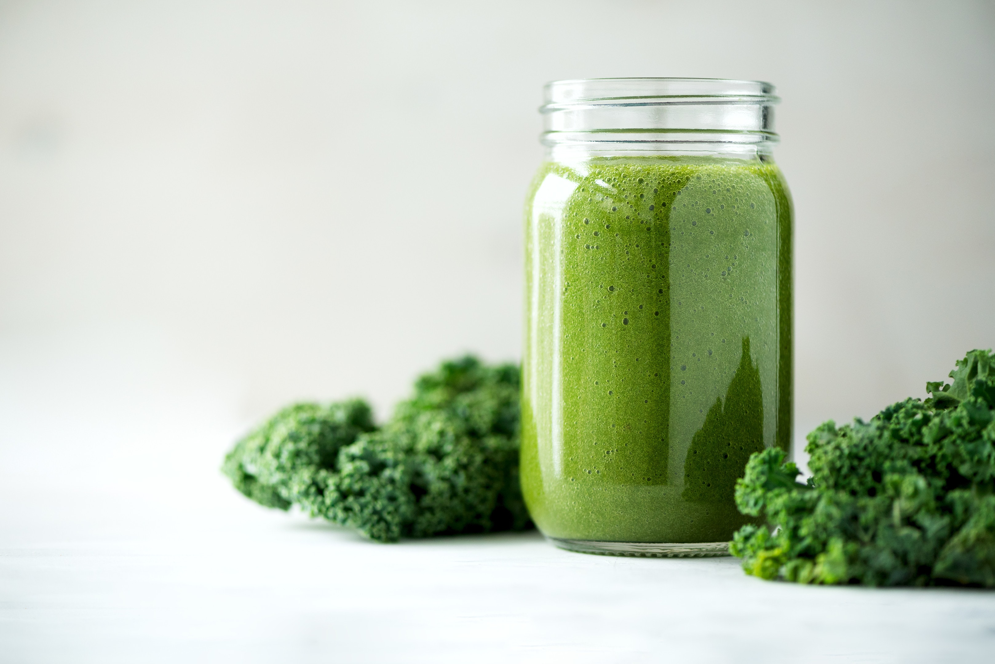Glass jar with green smoothie of kale leaves lime apple kiwi grapes banana avocado lettuce