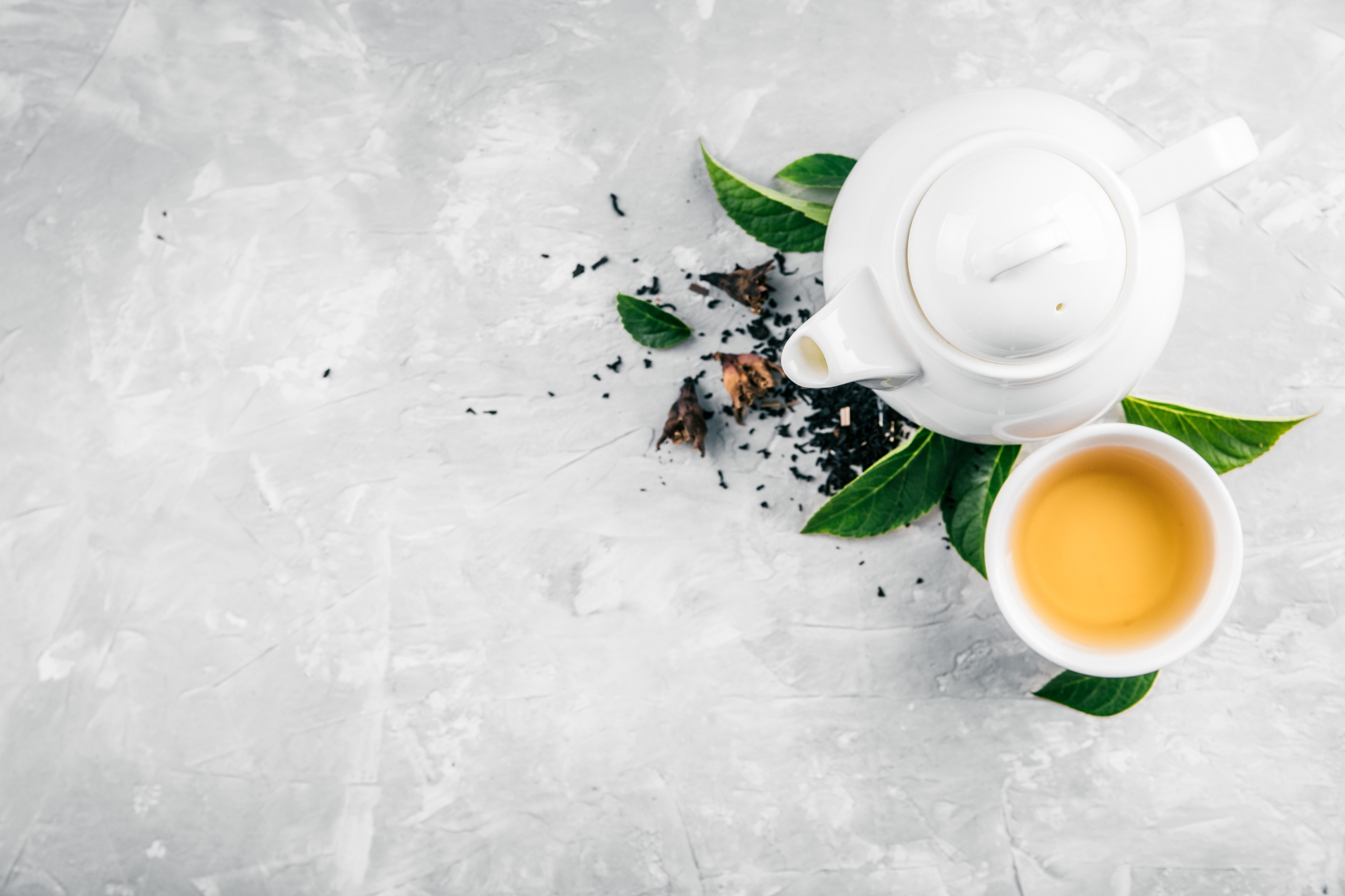 Herbal tea cup and teapot on concrete background