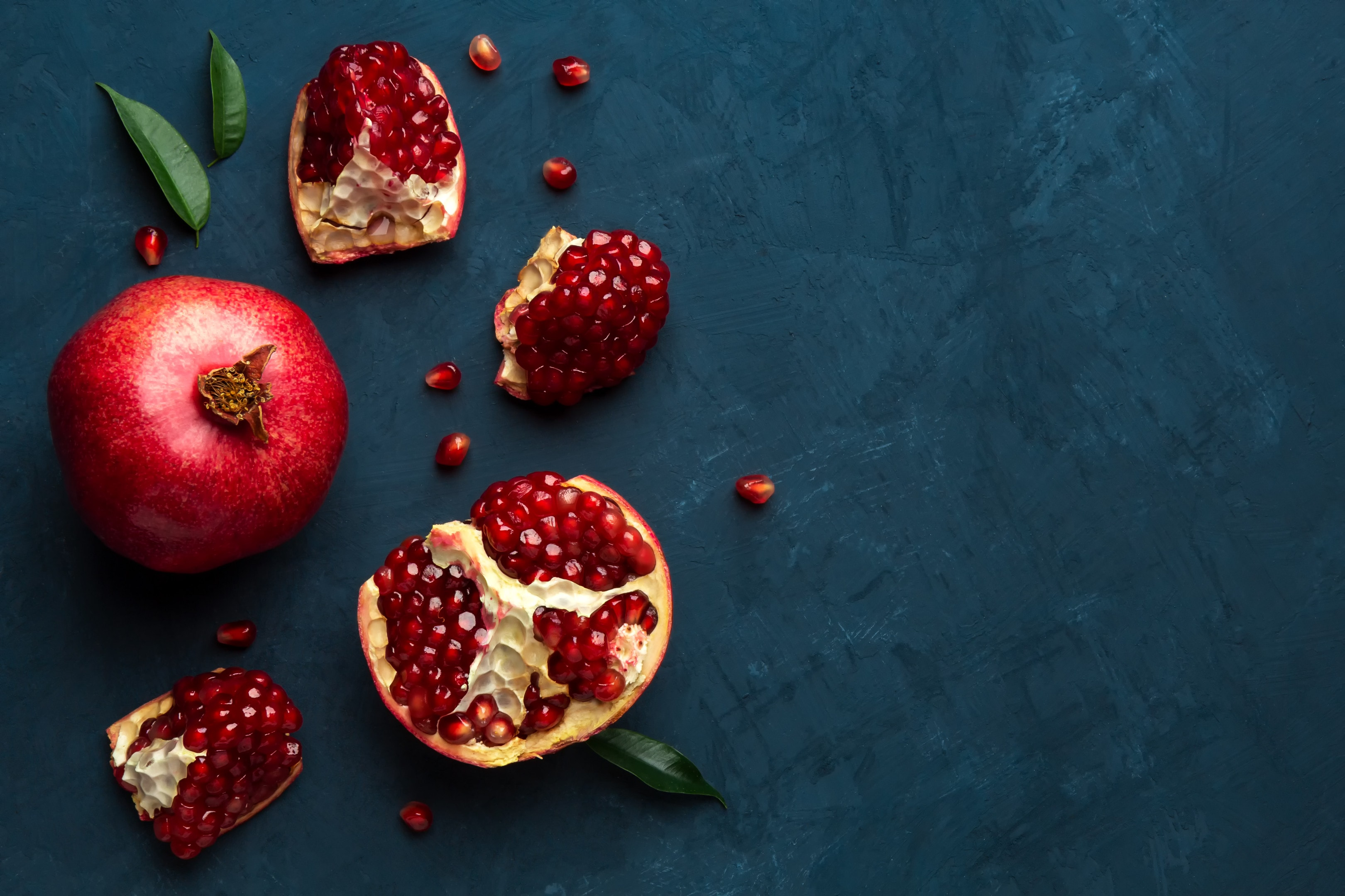 Juicy fresh pomegranate on blue wooden table